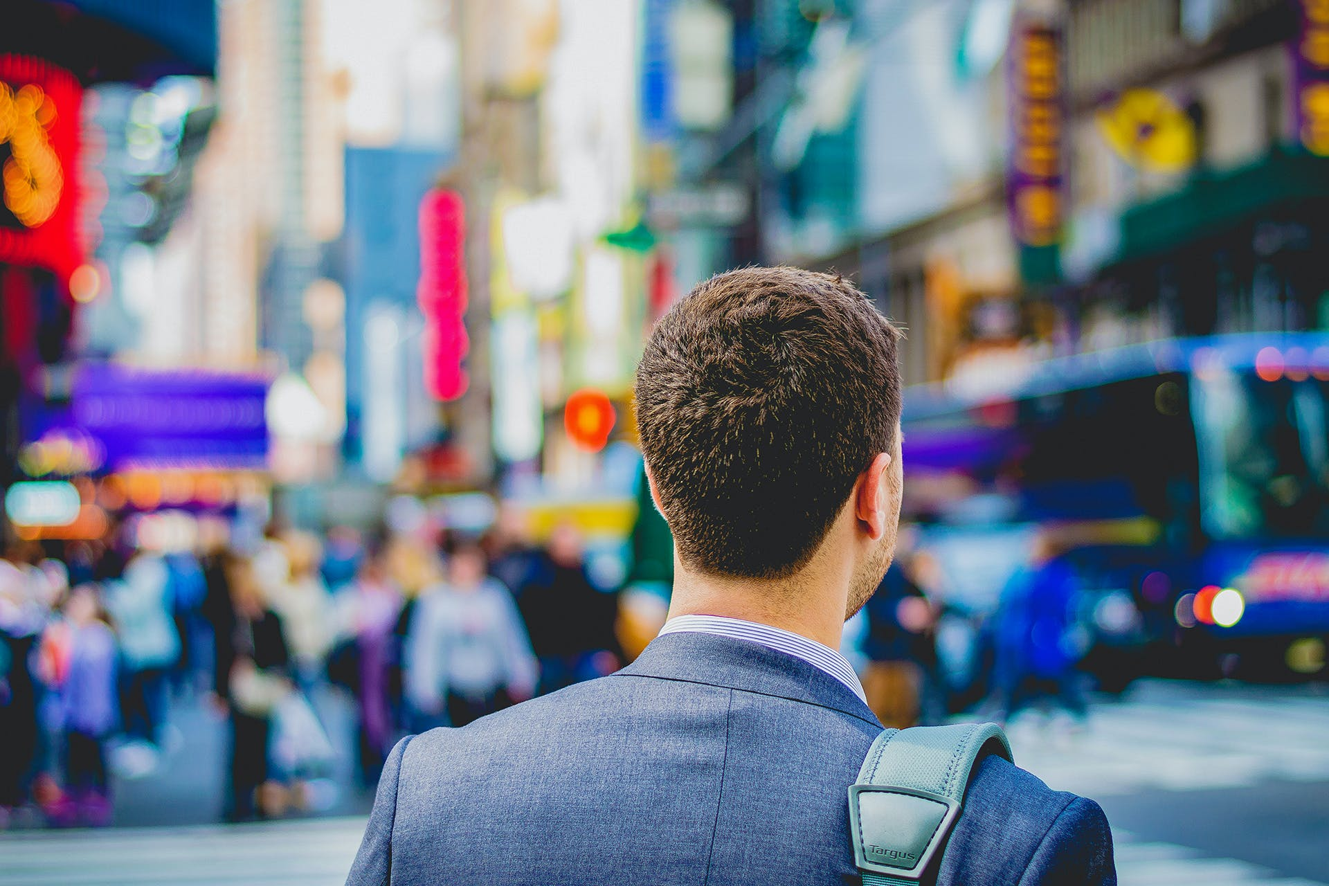 Man in a cityscape with a satchel and suit.