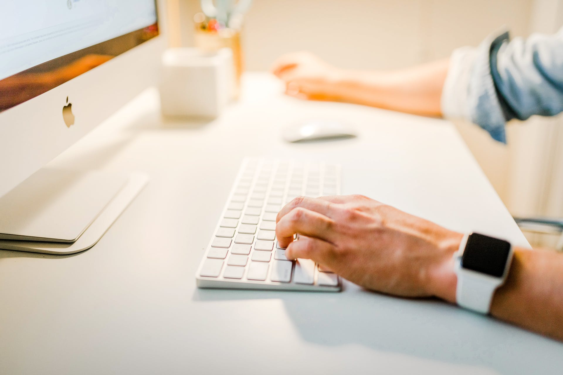 person wearing apple watch typing on a keyboard on their desk