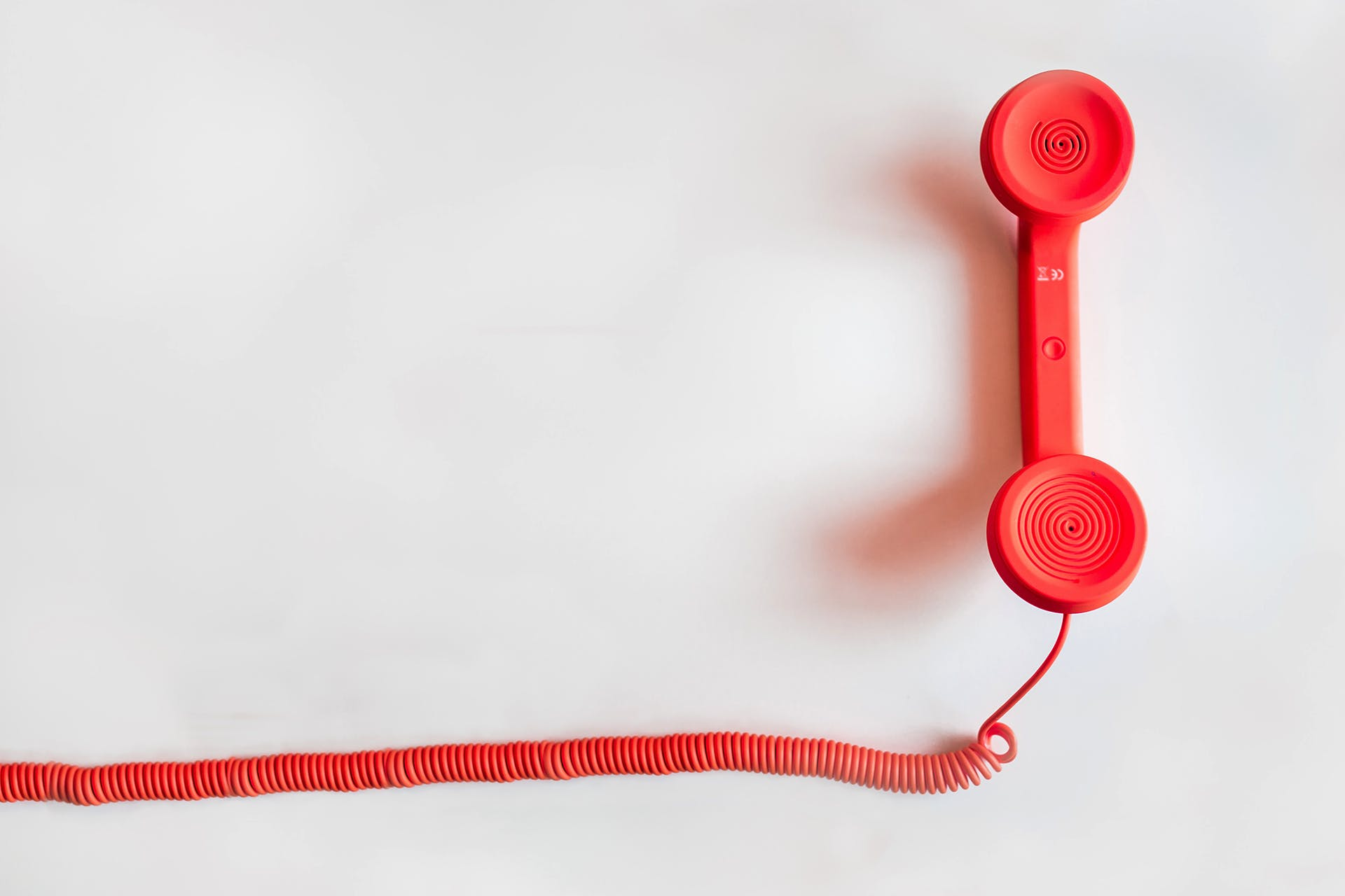 Red telephone against a white background