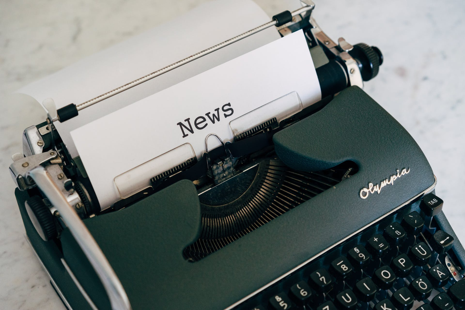 black typewriter with the text of news on paper
