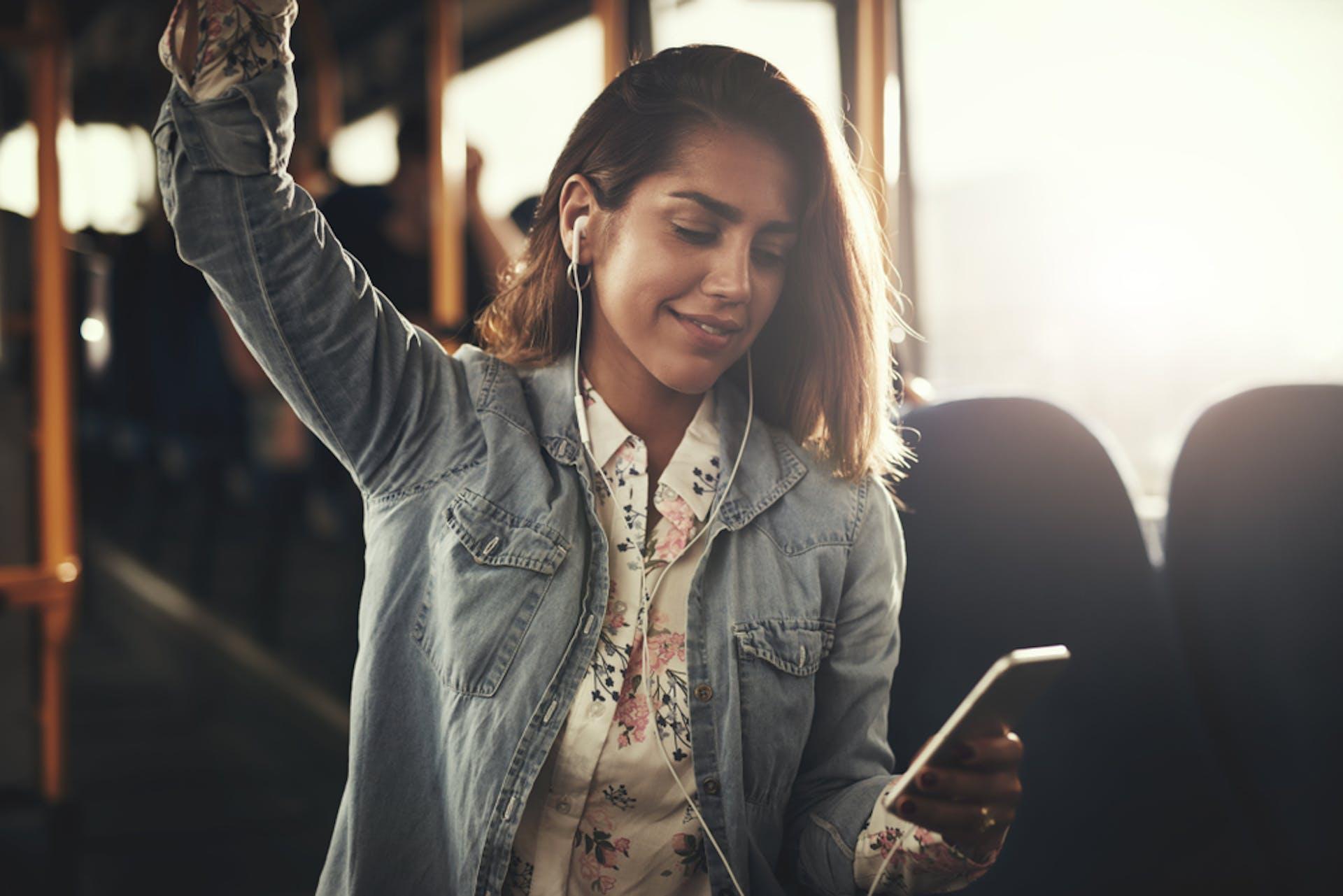 Eine junge Frau hält sich im Bus fest und schaut lächelnd auf ihr Smartphone