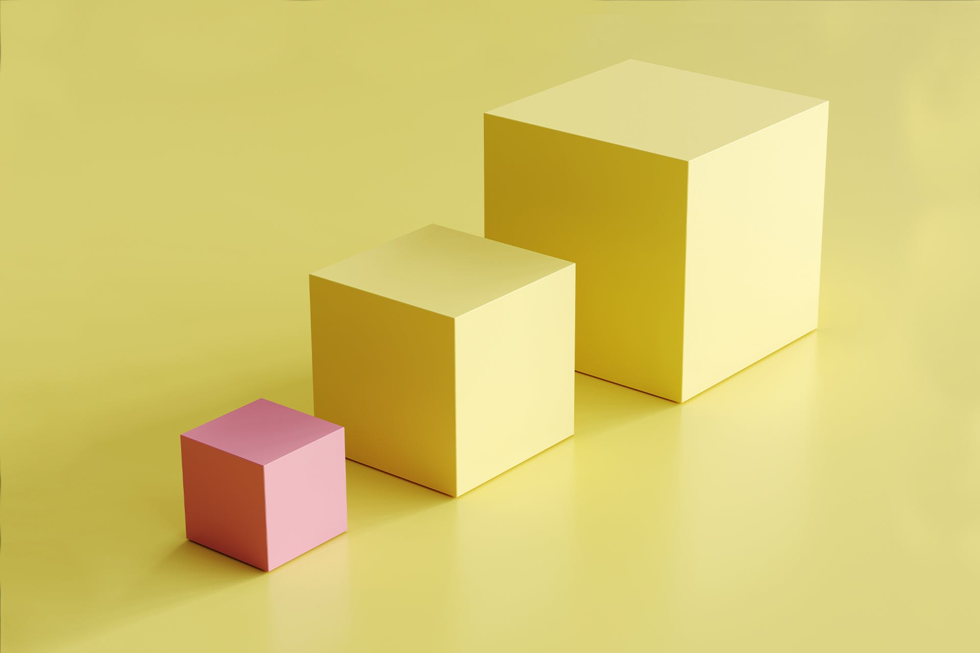 A set of blocks: two large yellow cubes and a smaller pink cube. The pink cube clearly stands out from the other yellow cubes, which makes this image the perfect fit for our blog on brand extensions and how to include them in your strategy.