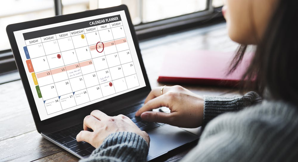 woman typing on a laptop with a social media content calendar on the screen