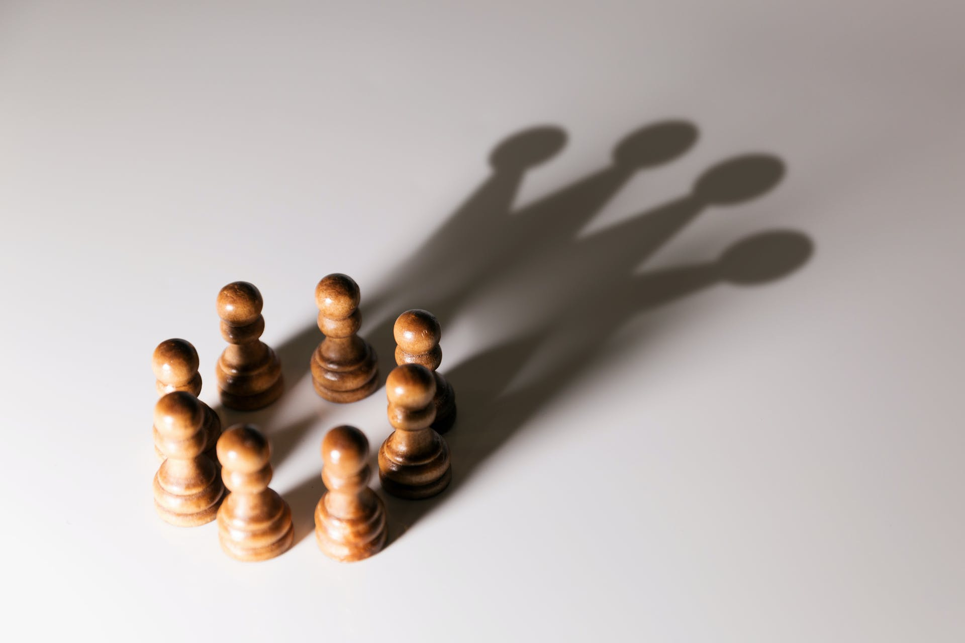 Chess pawns in a circle, with a shadow projecting the image of a crown.