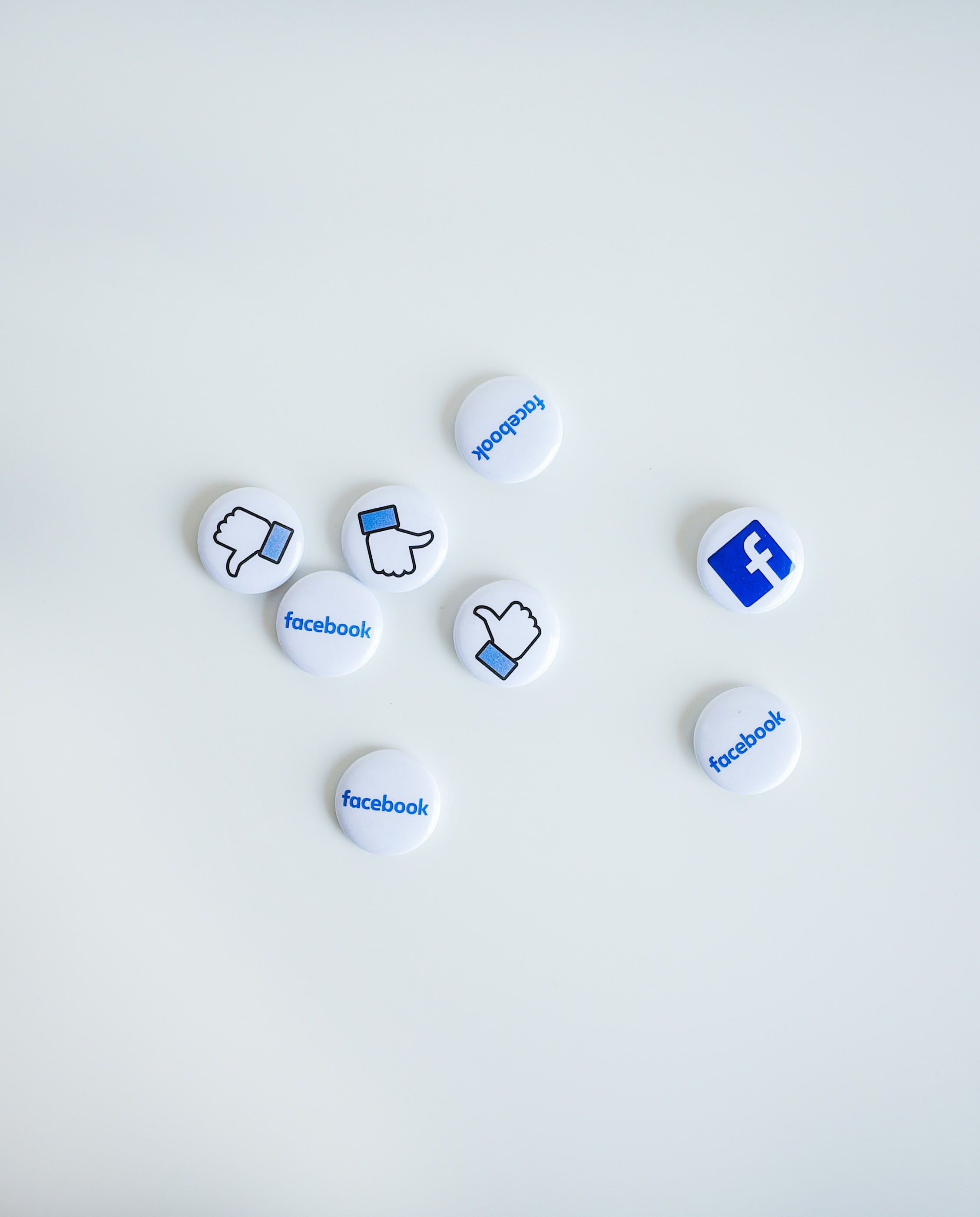 facebook logo and like button on white thumbnails on a white table