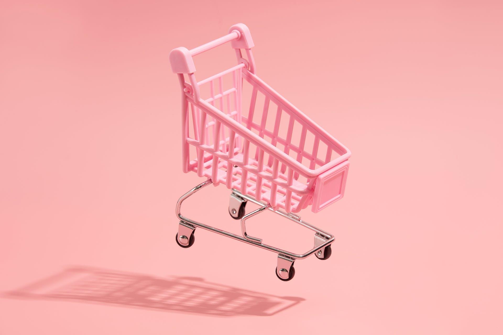 Pink miniature grocery cart on light pink background. Blog post on transactional marketing vs relationship marketing