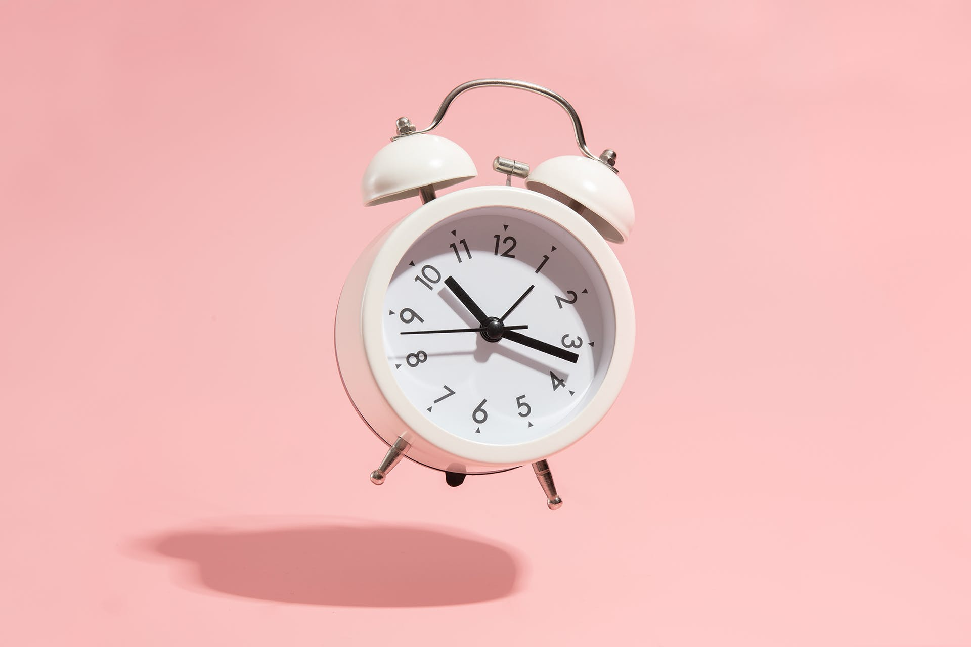 A white alarm clock is floating in the air because it is ringing so hard. This alarm clock was set to go off to remind us of the importance of real-time marketing in our strategies.