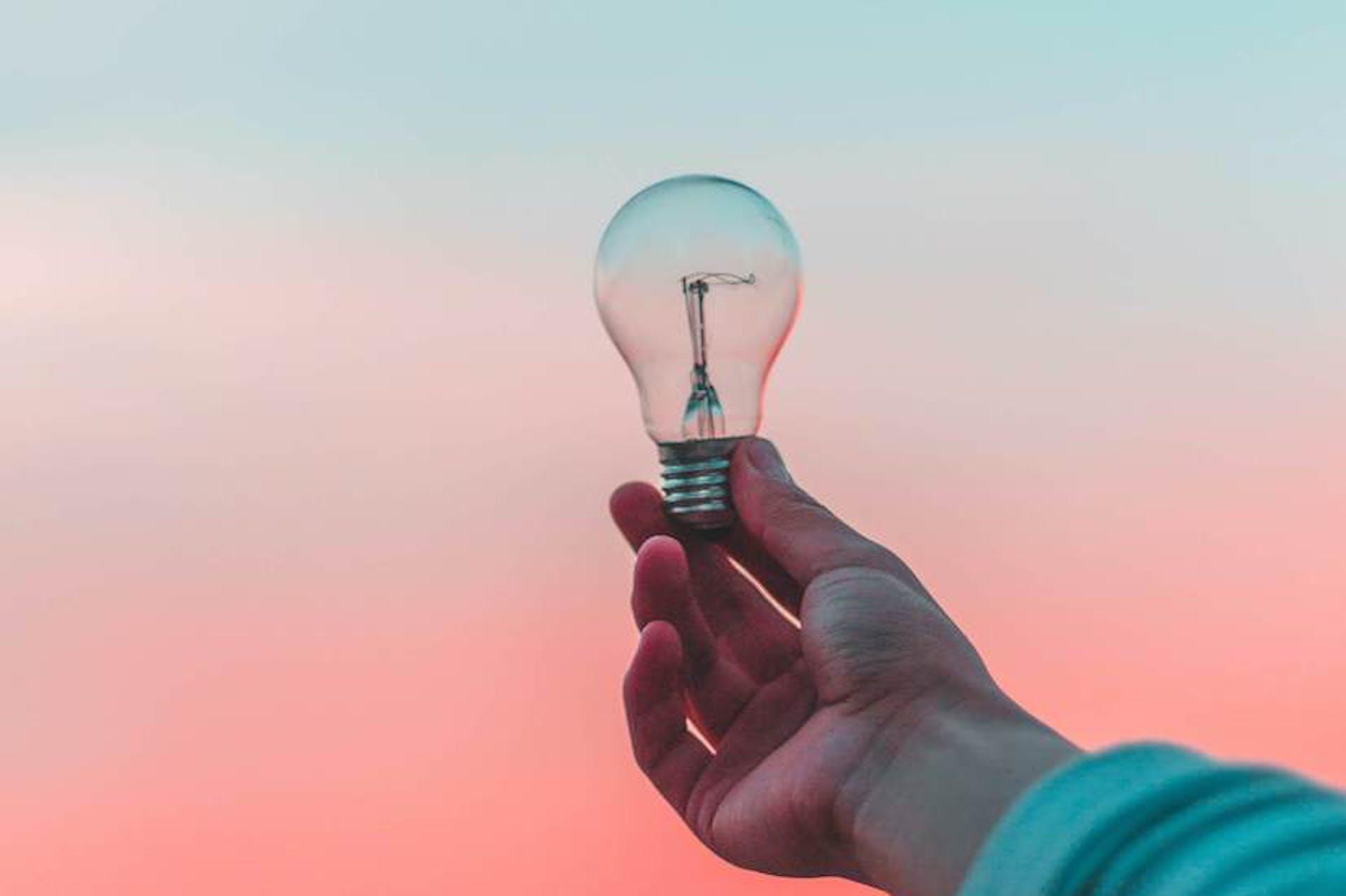 Man sieht eine ausgestreckte Hand, die eine Grlühbirne im Sonnenuntergang hält - als Metapher für unseren Beitrag zu Marketing Trends 2021