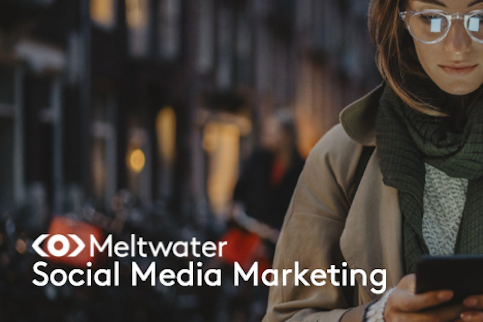 Meltwater Social Media Marketing Frau mit Brille auf der Straße schaut auf ihr Smartphone