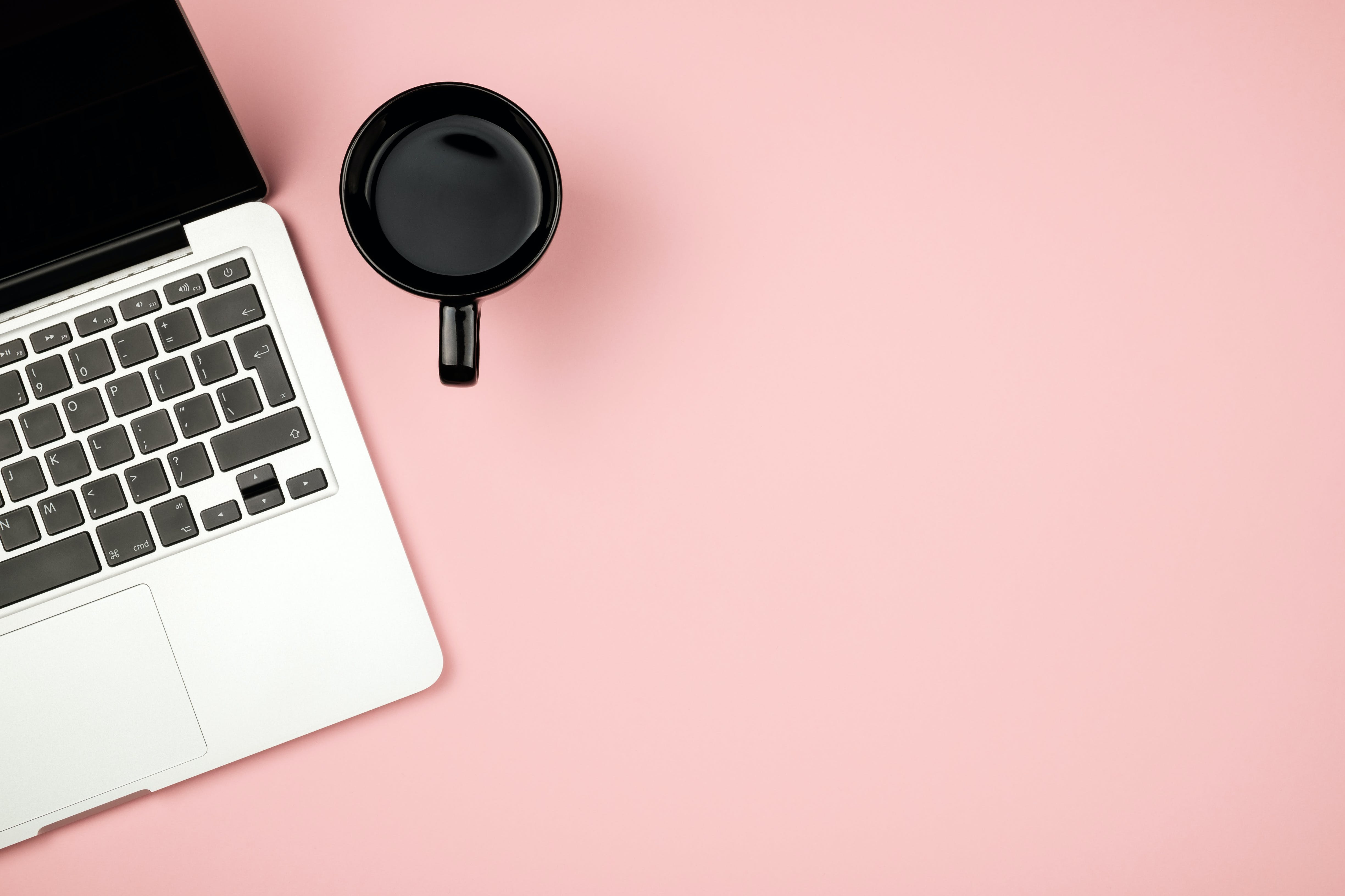 overhead photo of a laptop and coffee mug on a pink surface