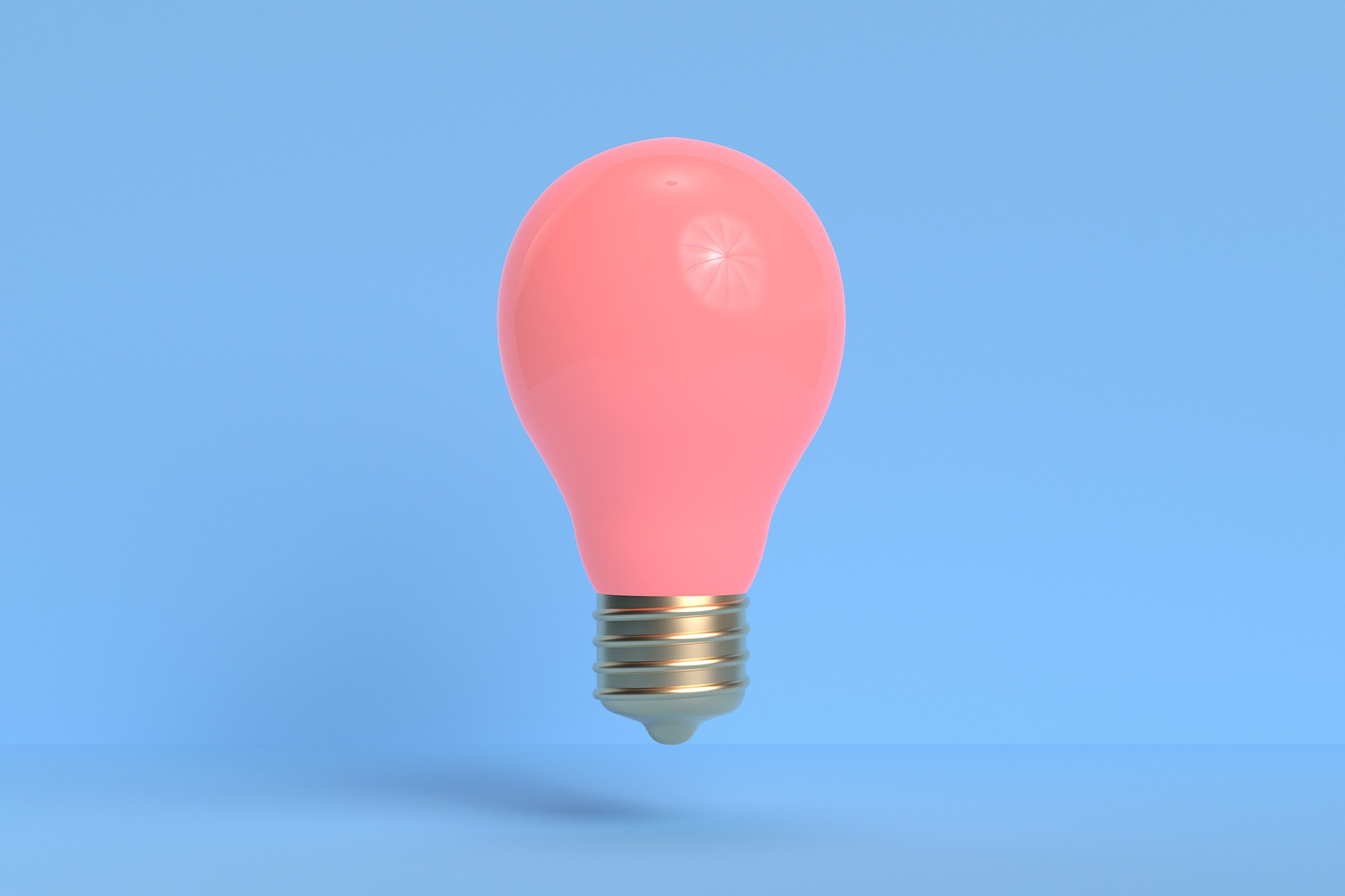 A bright pink lightbulb hovering in the air in front of a pale blue background. This image is used to describe a blog post outlining several ideas on how to use social walls in your marketing campaigns.