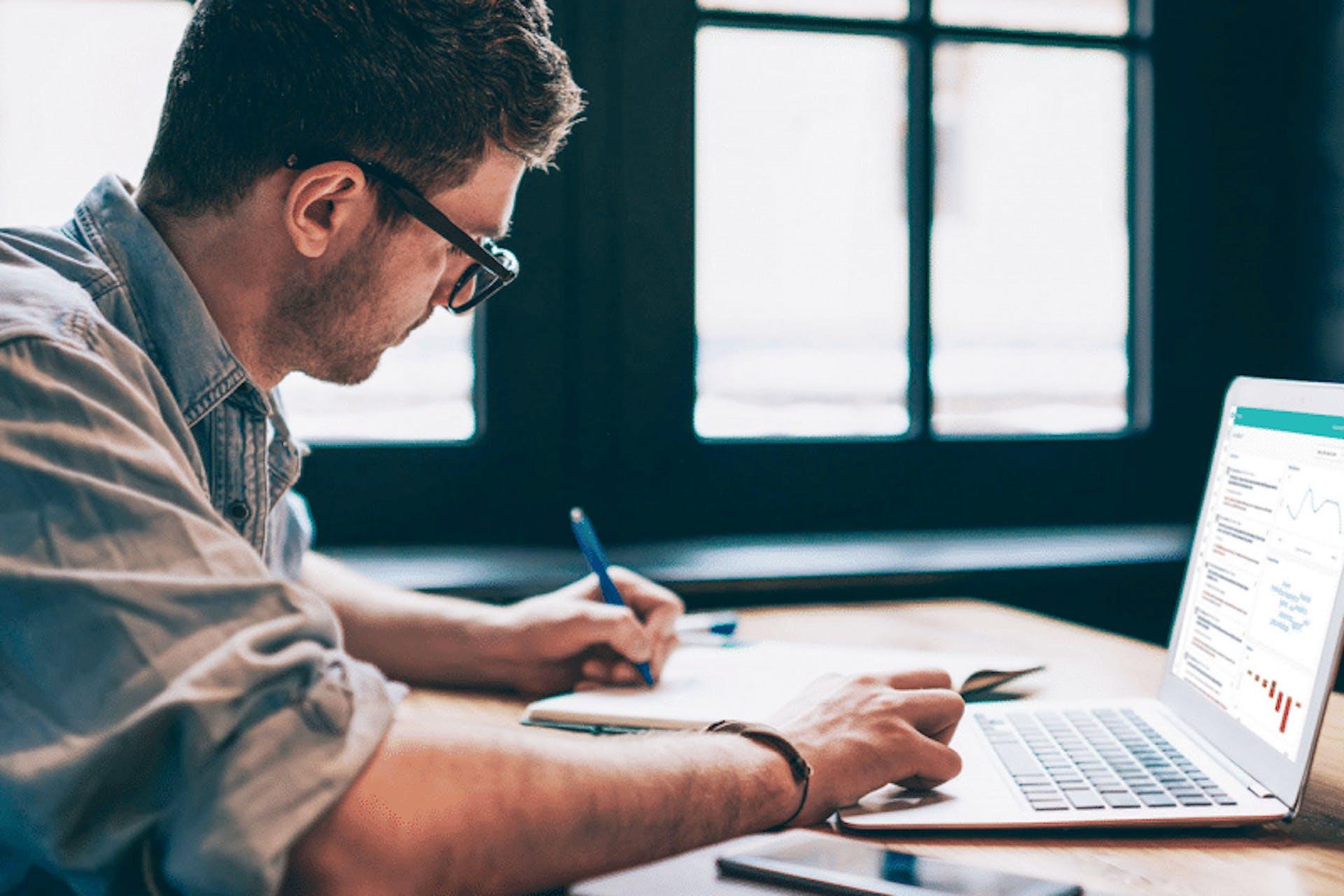 Man sieht einen jungen Mann mit Brille an seinem Schreibtisch sitzen. Er schreibt und arbeitet an seinem Laptop, auf dem die Meltwater PR Suite geöffnet ist. Dabei schaut er sich PR Reports an.