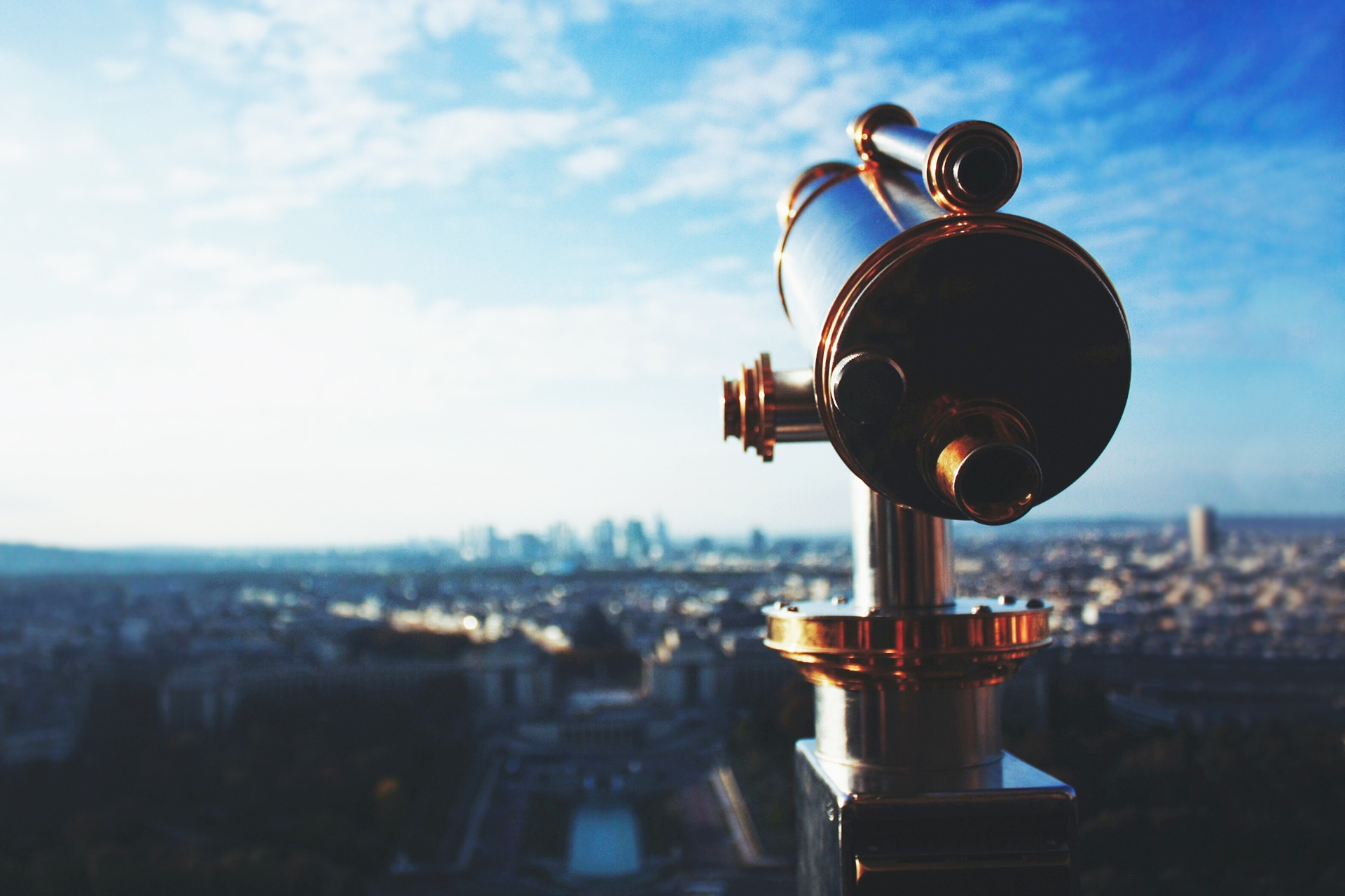 A close-up image of a telescope positioned toward a city in the background. This image is being used as a thumbnail for a blog explaining how to identify a single source of truth for marketing data
