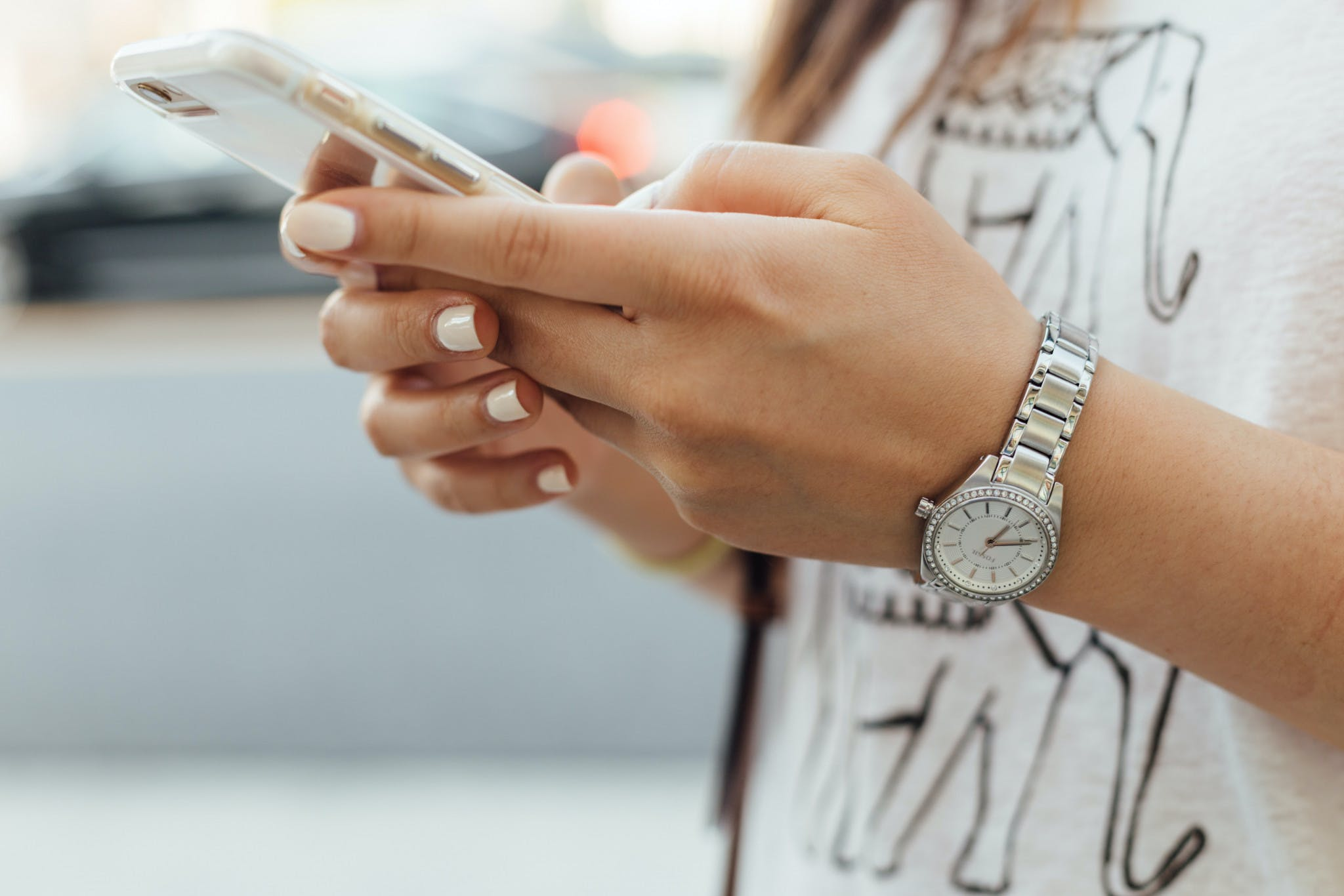 woman with a silver watch typing on her mobile phone
