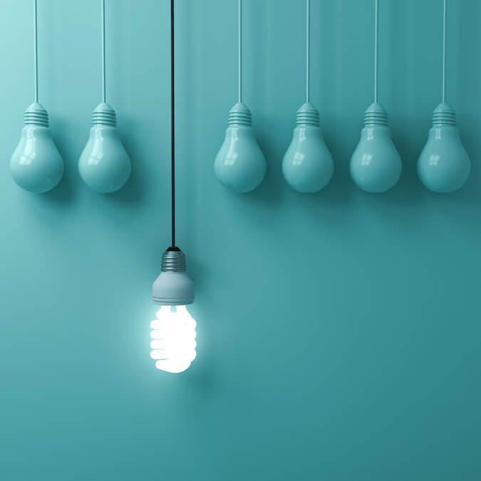 Man sieht sechs türkise Glühbirnen vor einer gleichfarbigen Wand hängen. Eine siebt Glühbirne hängt weiter unten und leuchtet. Dies soll den Unterschied symbolisieren, den ein USP für ein Unternehmen machen kann.