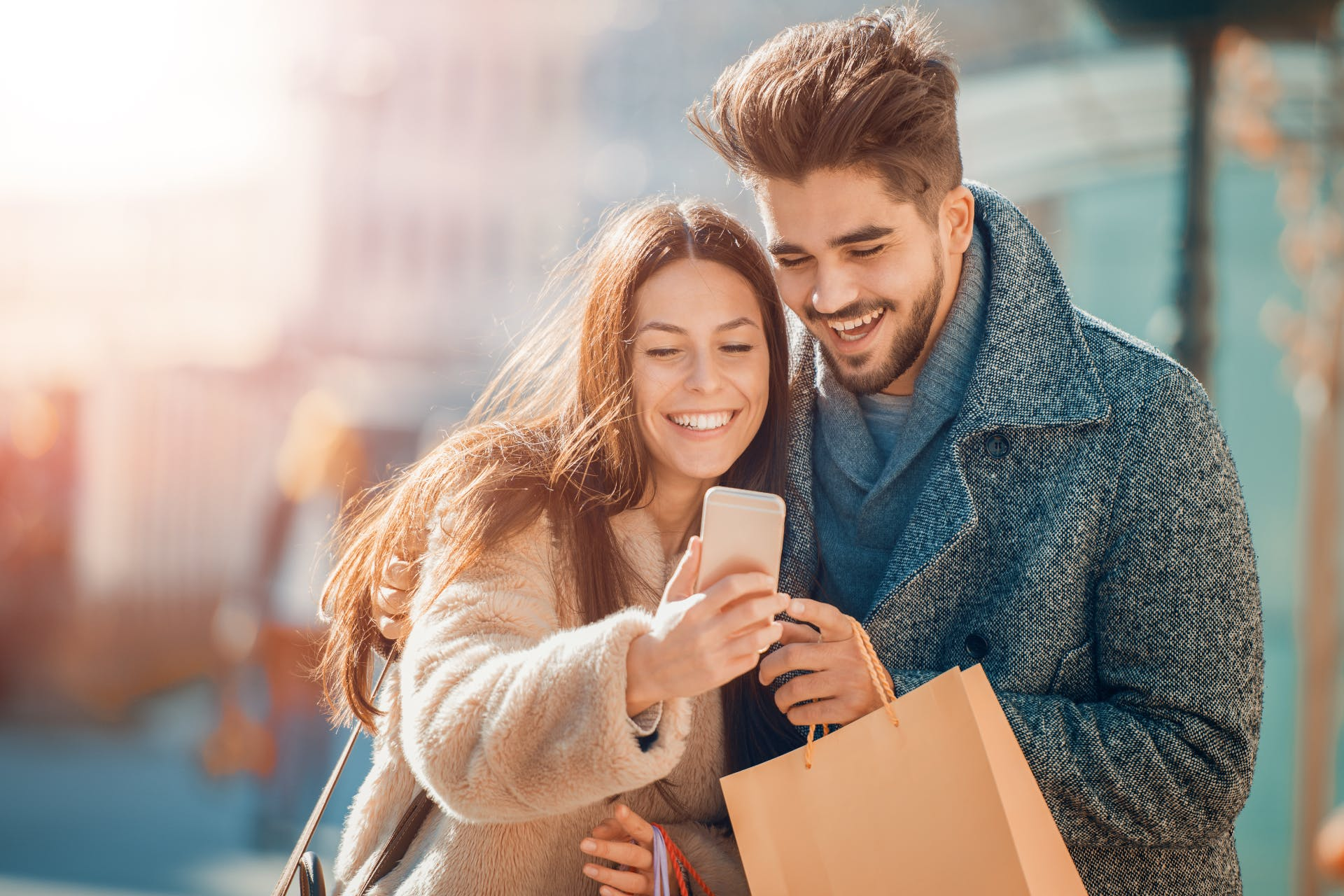 Couple holding shopping bags scrolling through a mobile phone
