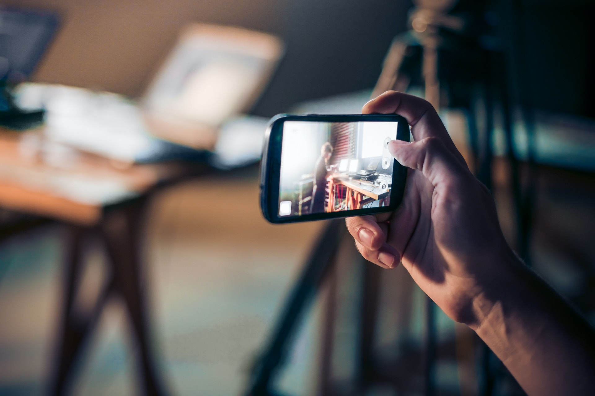 A hand holding a smartphone to shoot a video