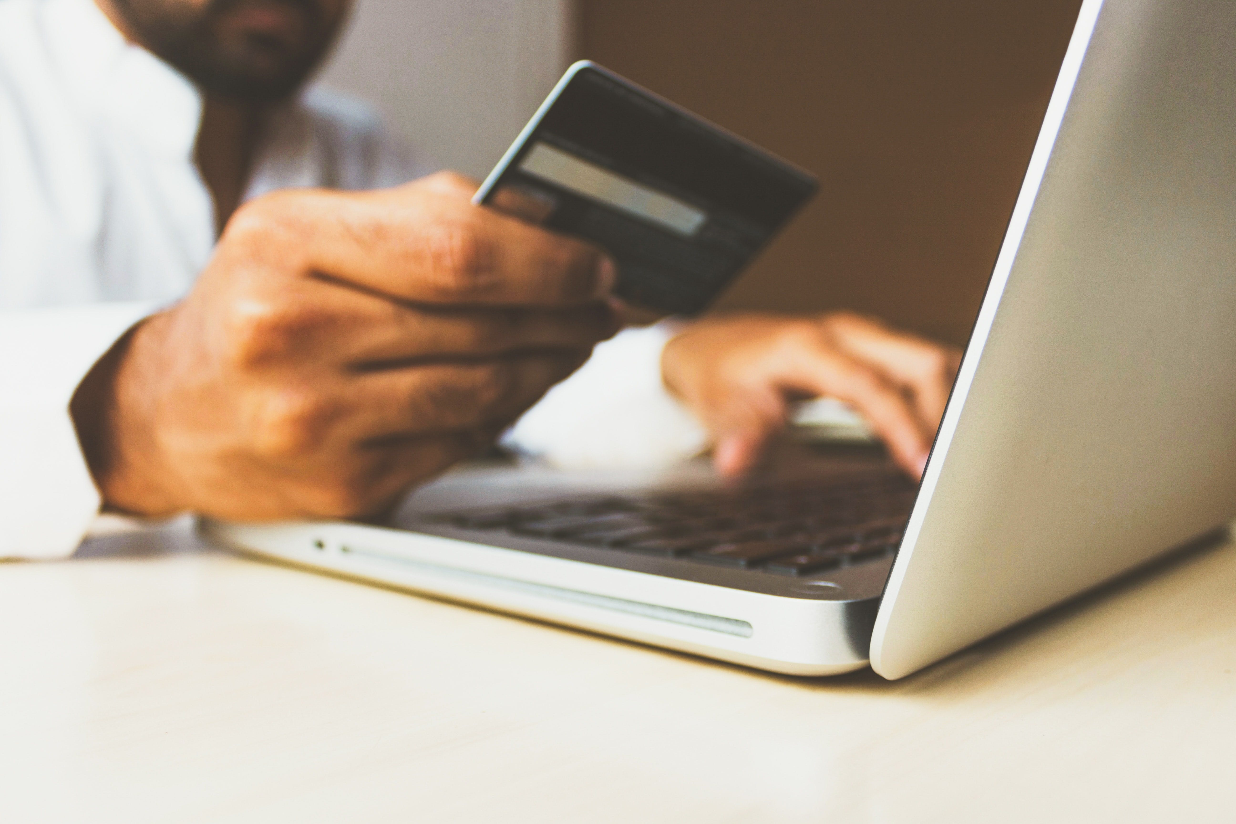Man holding credit card in front of laptop screen, ready to make a payment