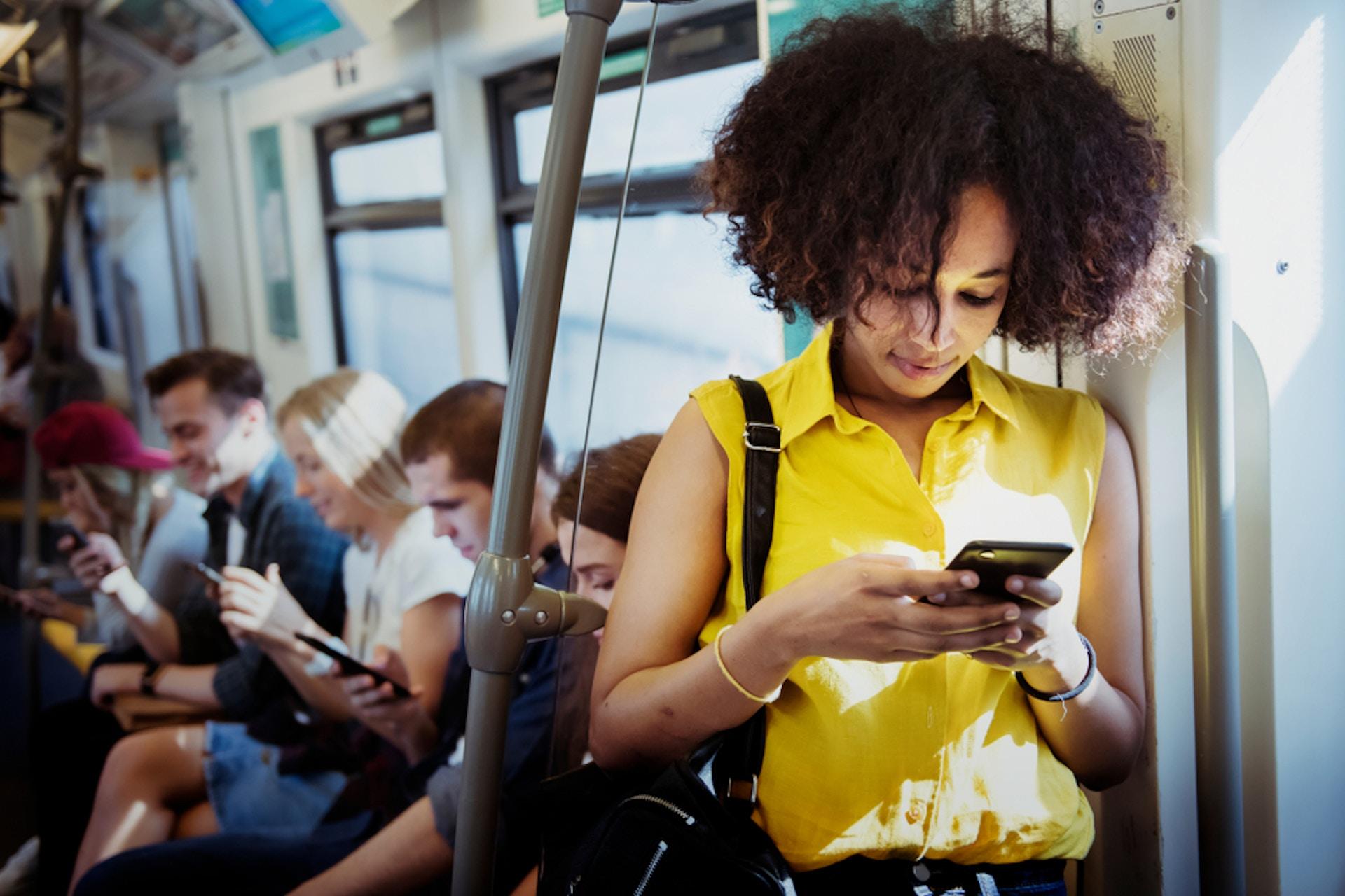 Junge Frau im Vordergrund in der Bahn an ihrem Smartphone, junge Menschen im Hintergrund an ihren Smartphones