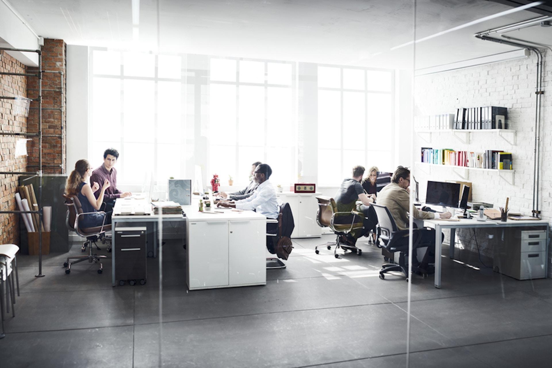 Foto Büro mit arbeitenden Menschen durch eine Glaswand fotografiert