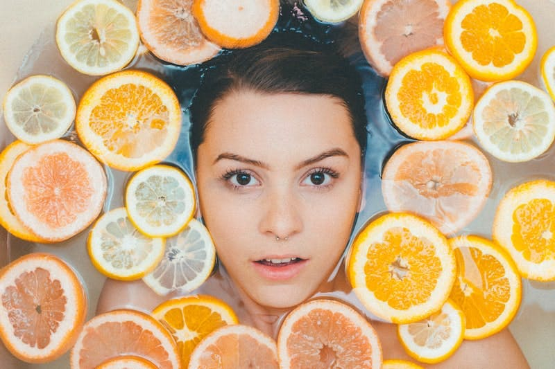 A woman surrounded by sliced lemons and oranges