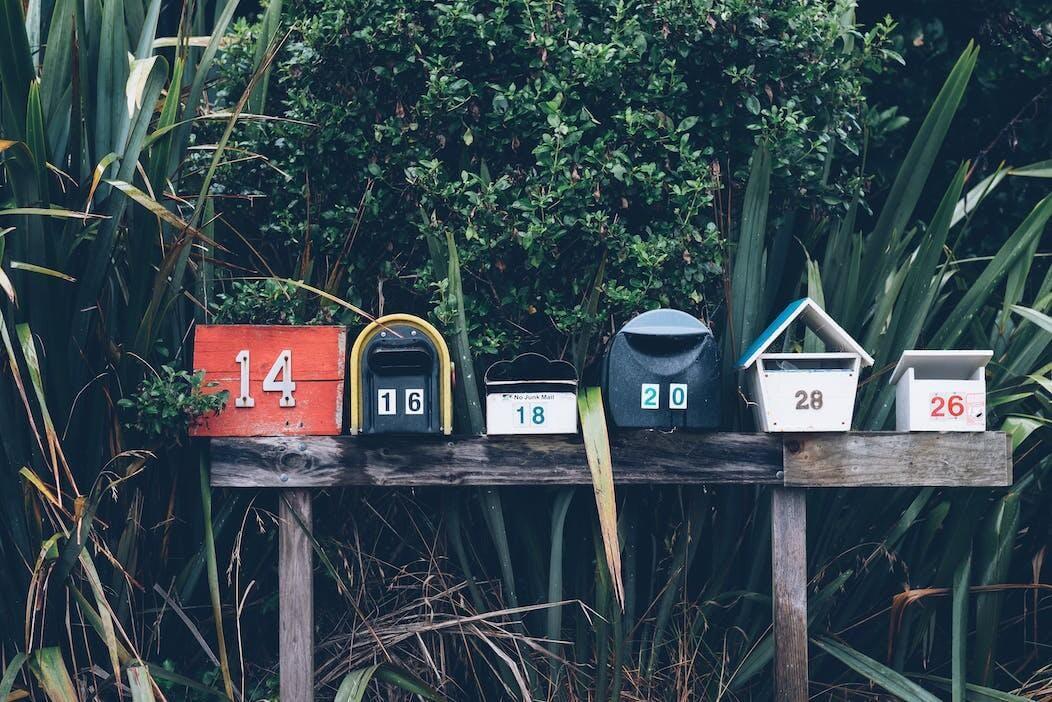 Man sieht ein Foto von mehreren hübschen Briefkästen, die auf einer Bank nebeneinander stehen.