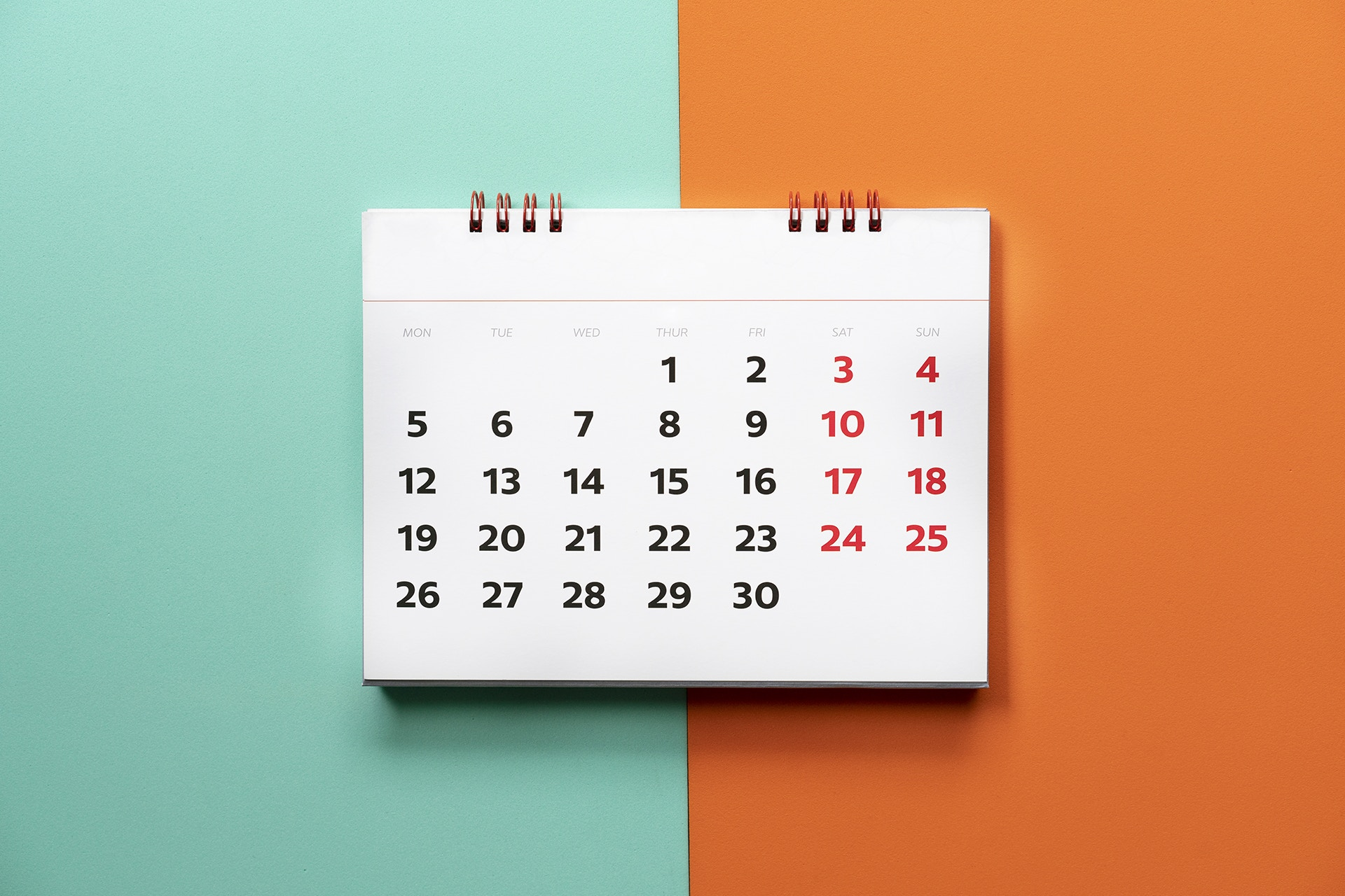 green and orange background with a calendar in the foreground