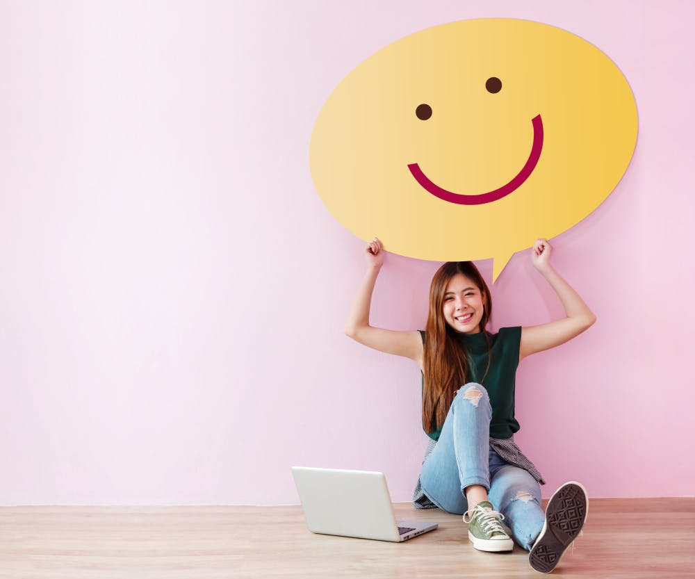 A young gril sitting in front of a laptop holding a large smiley face poster above her head.