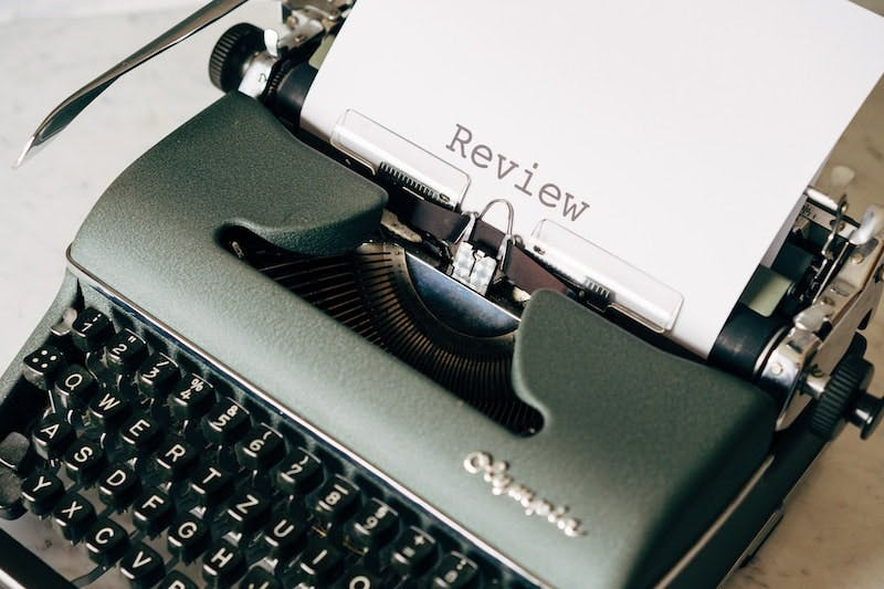 A green typewriter with a piece of paper displaying the word review