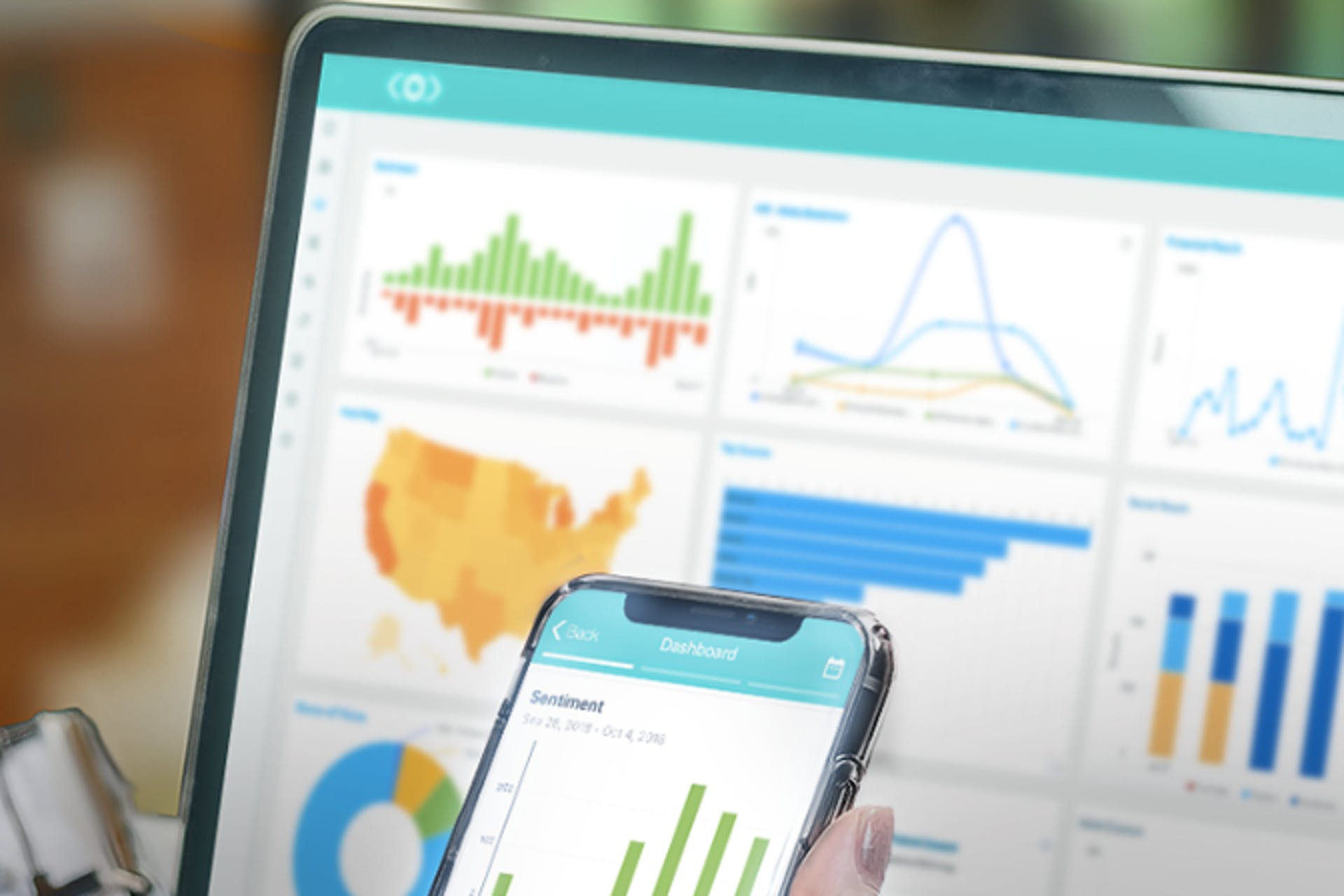 Laptop and cell phone both depicting charts and graphs.
