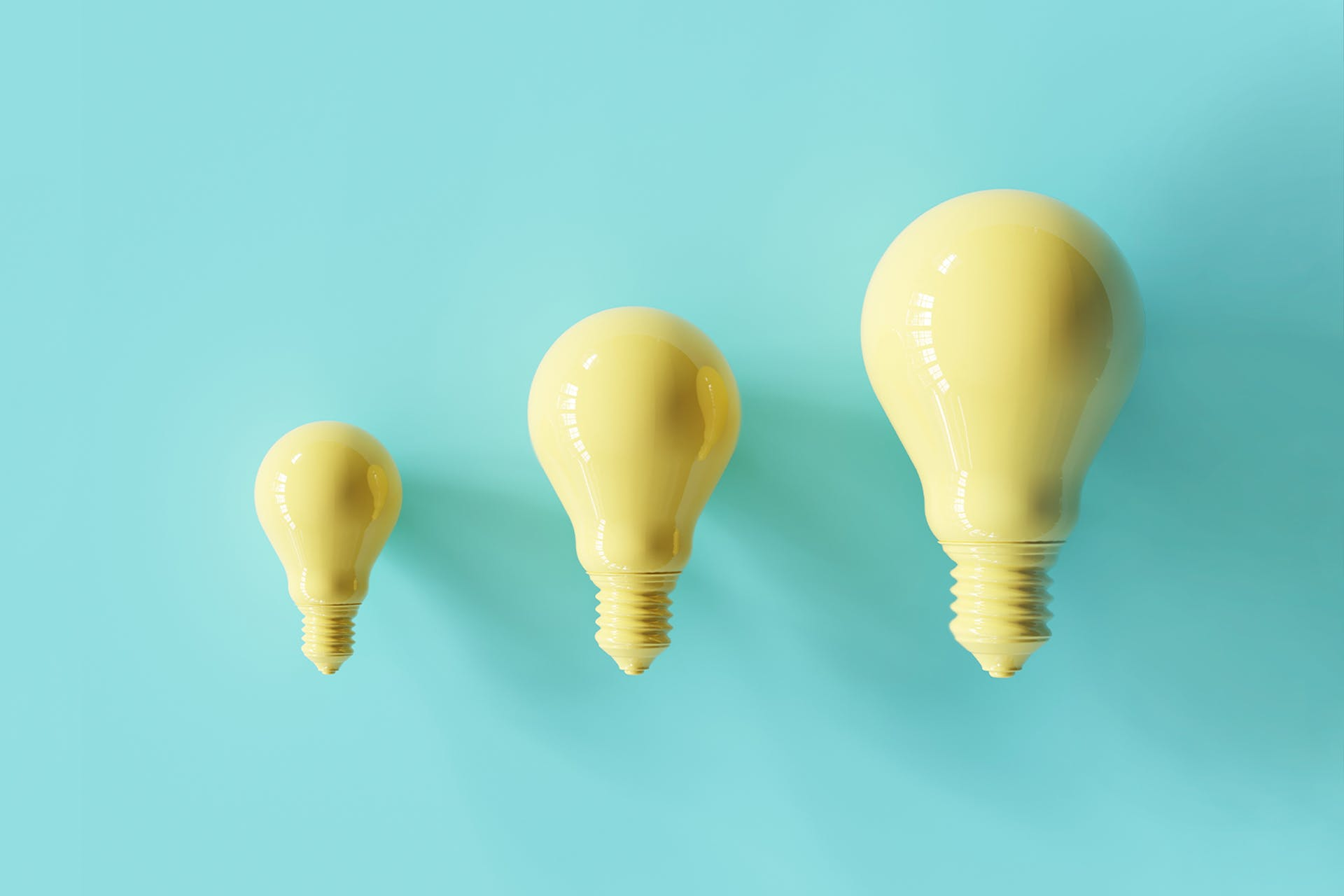 Three yellow lightbulbs lined up next to one another. The lightbulbs are three different sizes, but all the same shape.