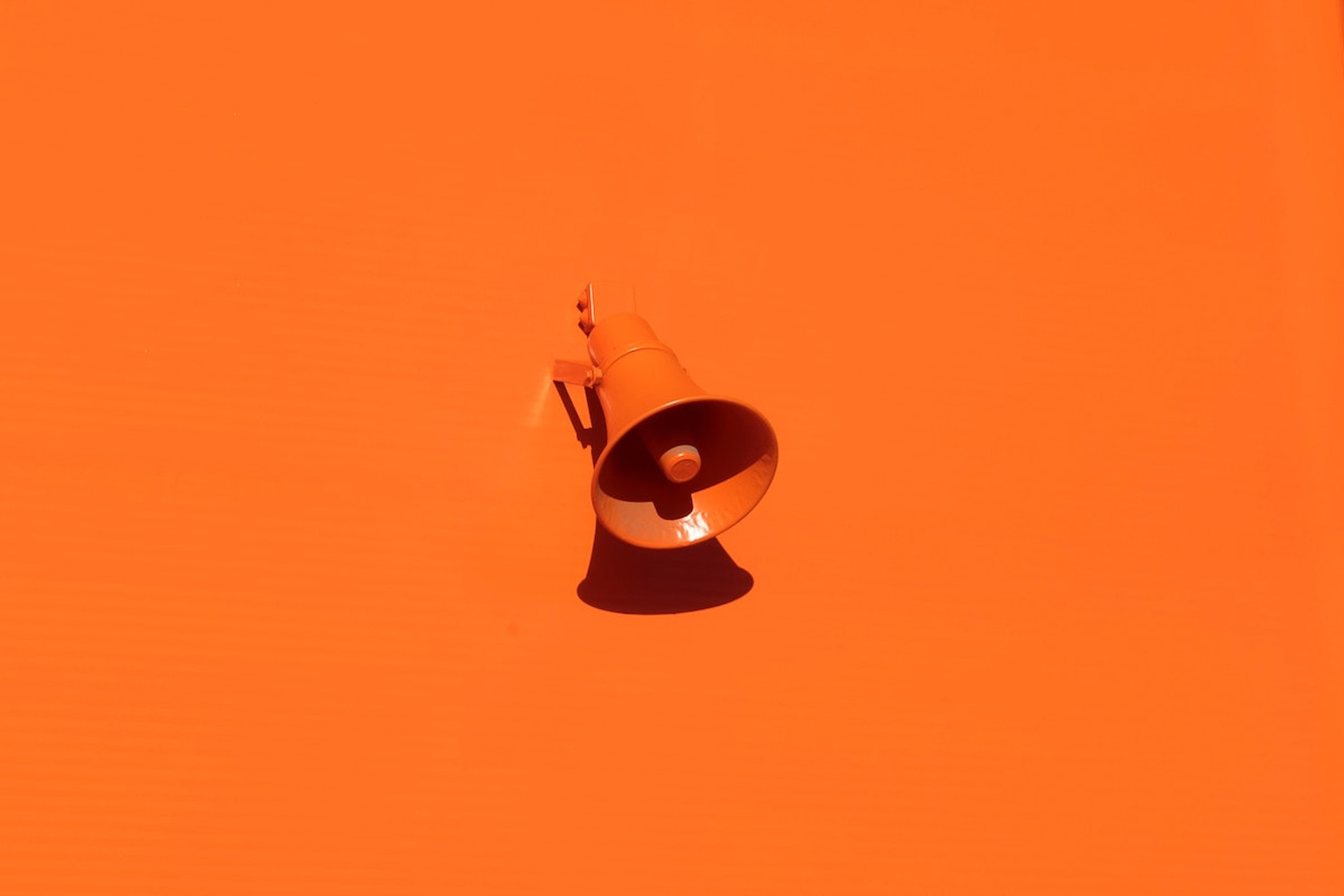 An orange megaphone on an orange surface