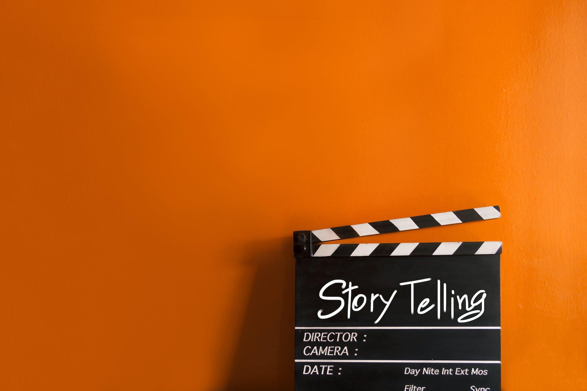 """Eine Filmklappe mit der Aufschrift """"Story Telling"""" auf einem orangenen Hintergrund"""