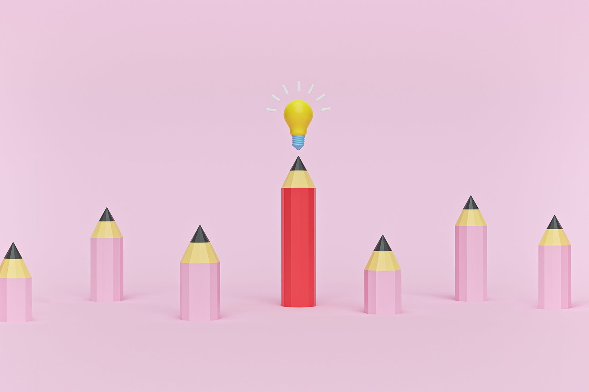 A group of six small pink pencils and a large red pencil with a lightbulb on top of it. This image describes the process a writer or marketer may go through when developing content marketing ideas.