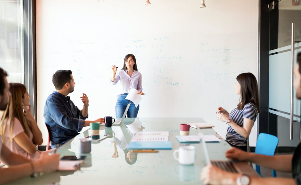 A woman presenting in front of a bunch of people sitting at a table