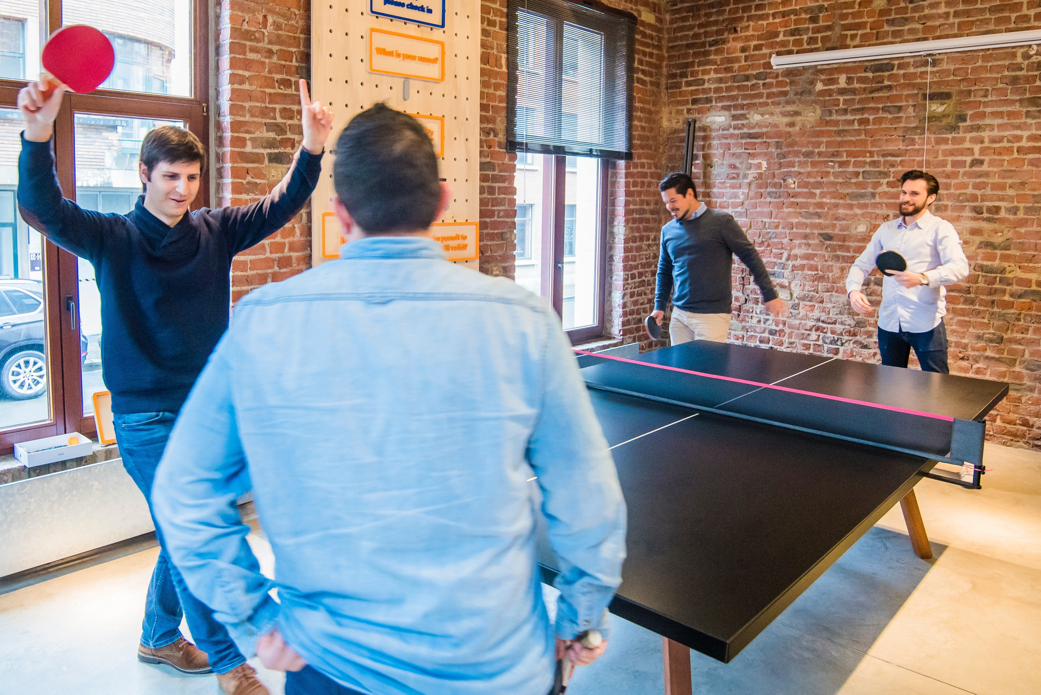 A group of four men playing ping pong in an office during a break. This is the type of in-office experience that can positively contribute to the employee brand.