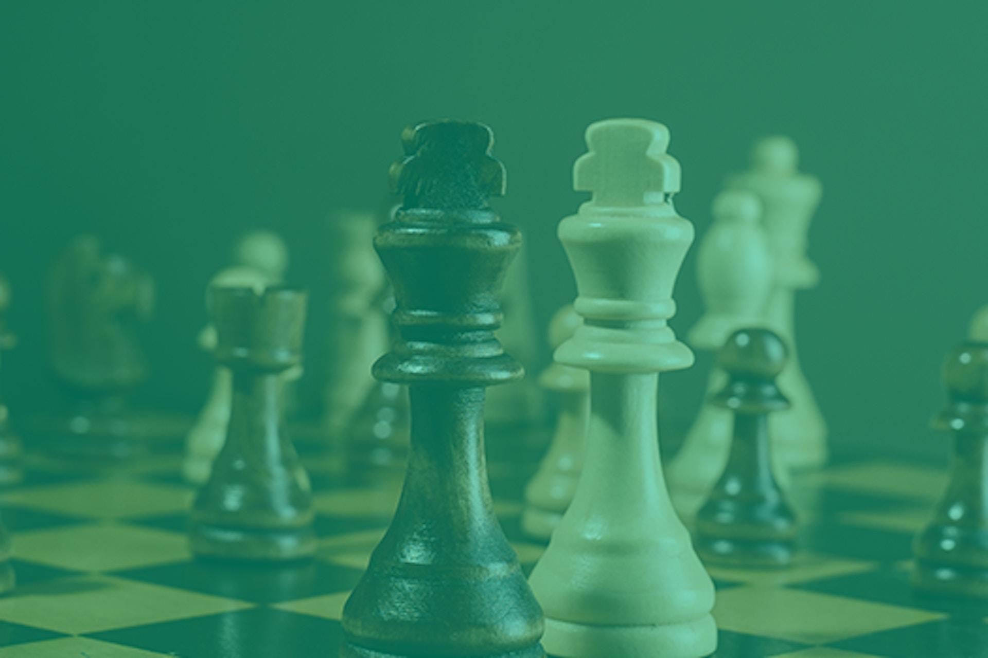 Man sieht ein Schachfeld mit den beiden Königinnen im Vordergrund. Das ist das Titelbild unseres Beitrags zum Thema Wettbewerbsanalyse.