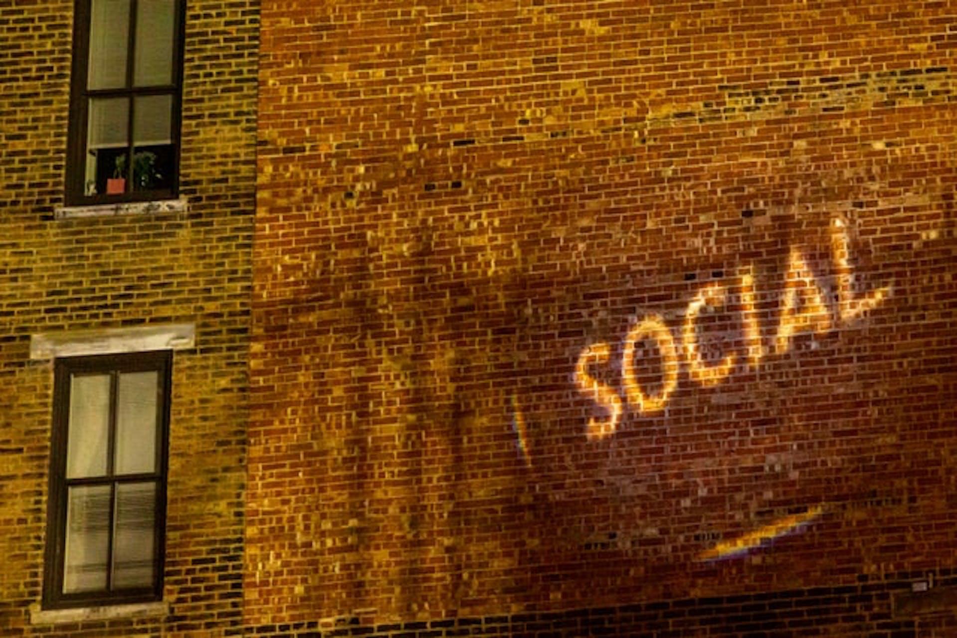 """Man sieht eine Backsteinwand eines Gebäudes, auf die das Wort """"Social"""" projiziert wird. Das Bild ist das Titelbild unseres Beitrages zu Social Media Walls."""