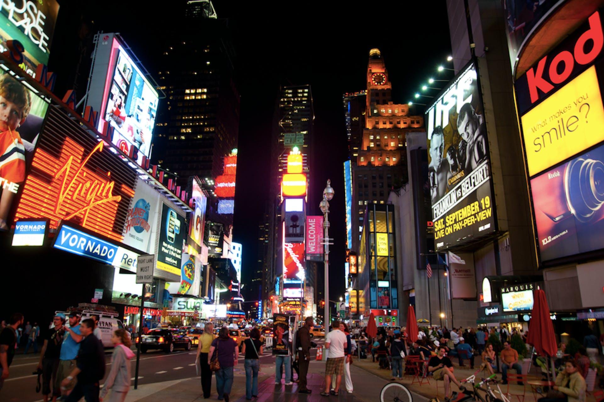 Man sieht einen Straßenzug bei Nacht voller Schaufenster und Marken, deren Schriftzüge leuchten. Dieses Bild ist das Titelbild unseres Beitrags zum Thema Co-Branding.