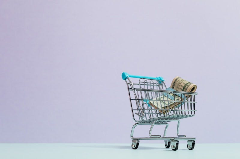 A small shopping cart with money in it