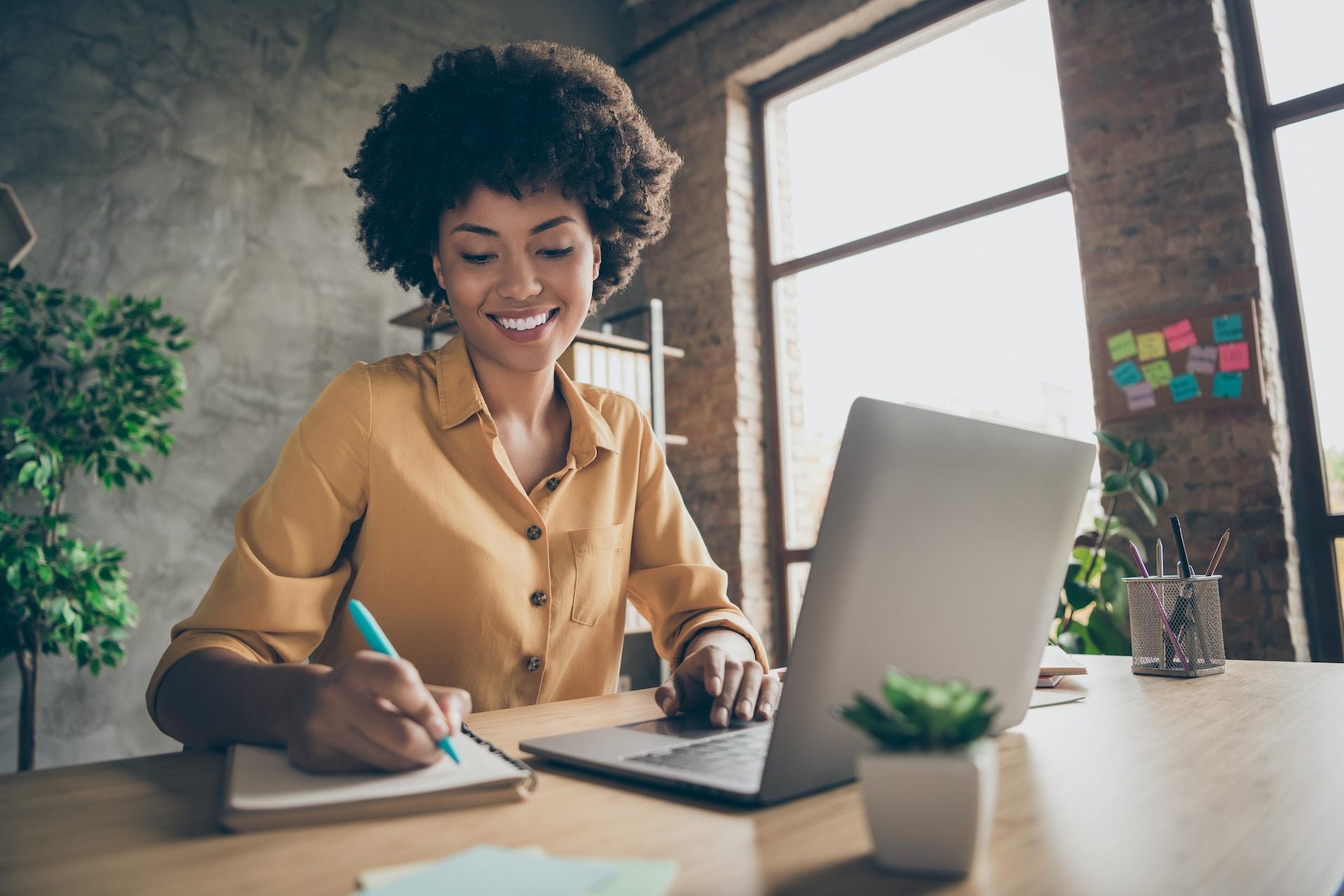 Man sieht eine junge afroamerikanische Frau an ihrem Laptop arbeiten
