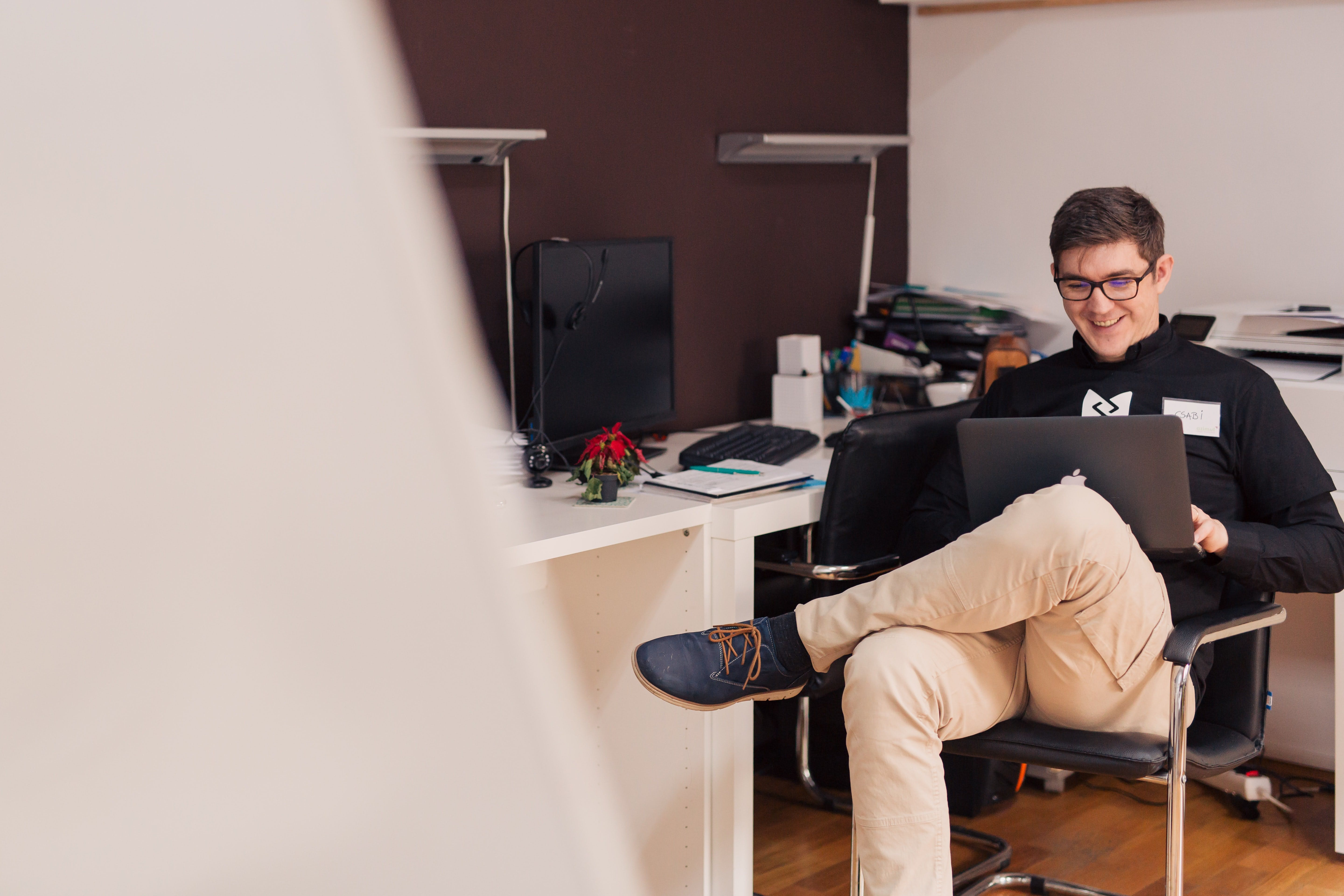man with glasses sitting on chair in the office using a macbook