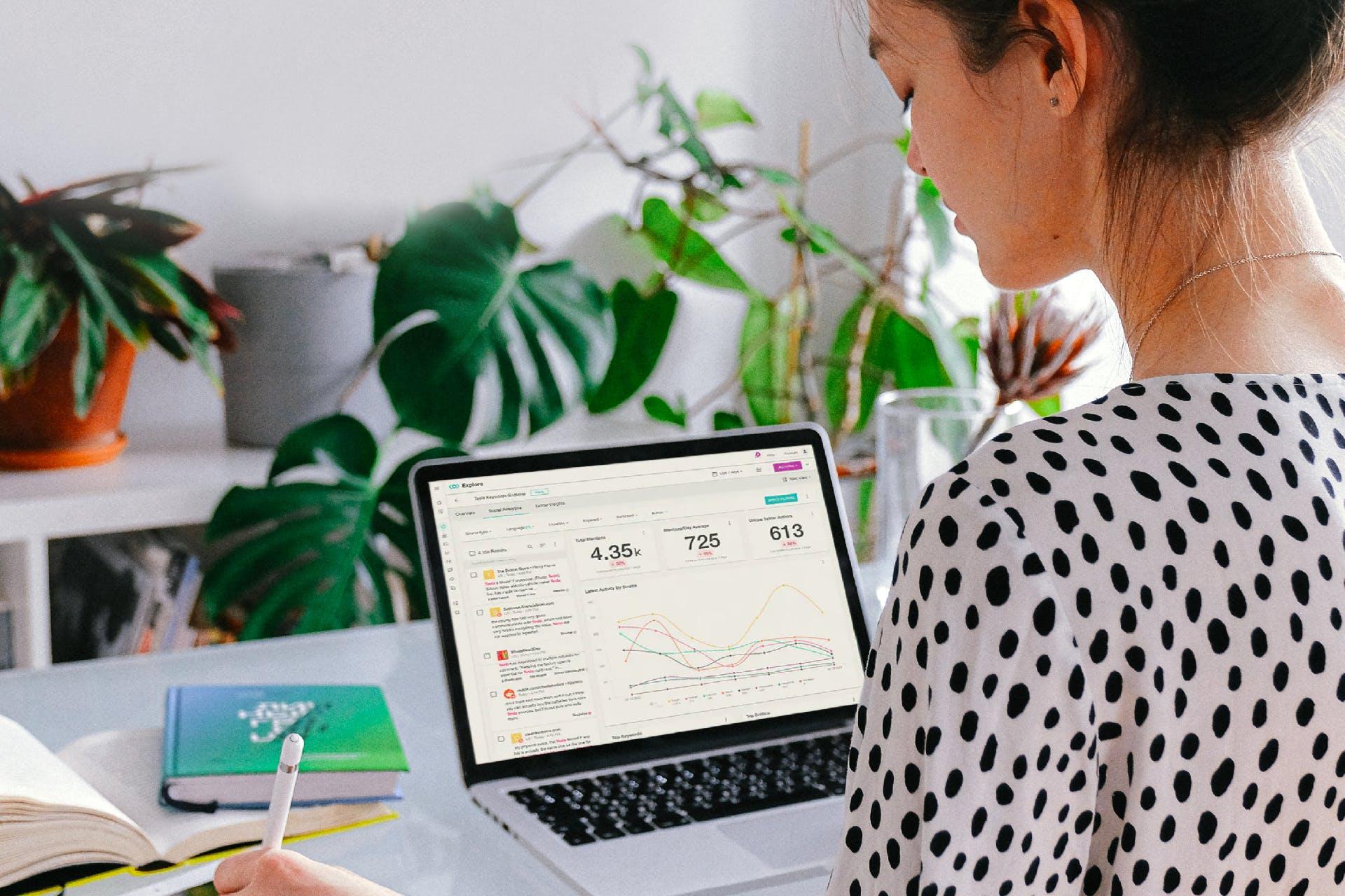 nainen tietokoneen edessä katsoo näytöltä data-analytiikkaa