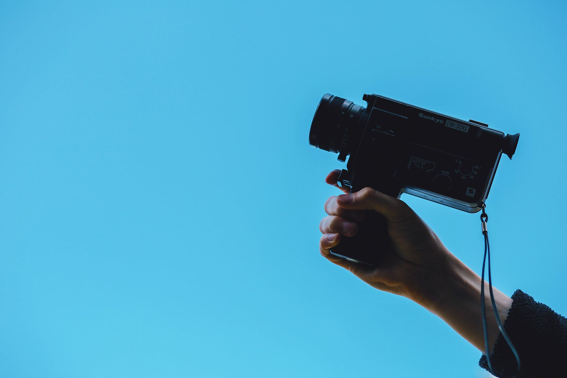 Woman's hand holding a camera like a gun over a blue background.