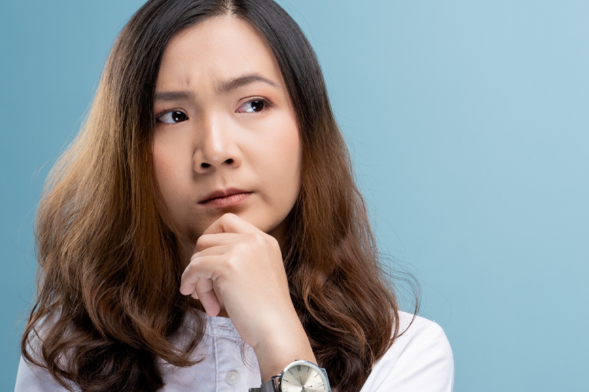 Young asian woman with her hand under her chin, listening, thinking, with a blue background.