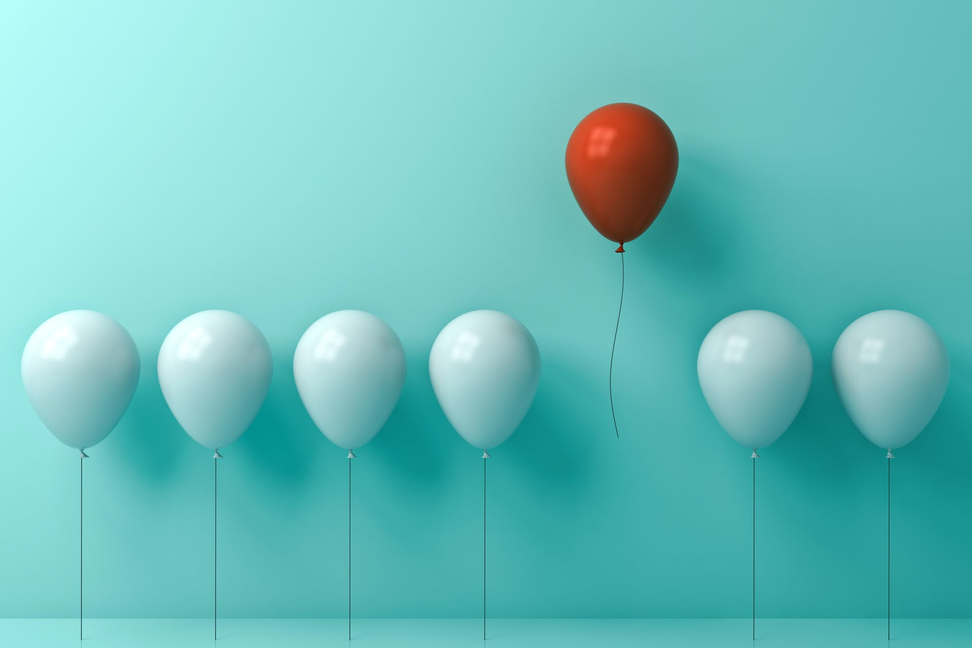 Image of white balloons with one red balloon flying away