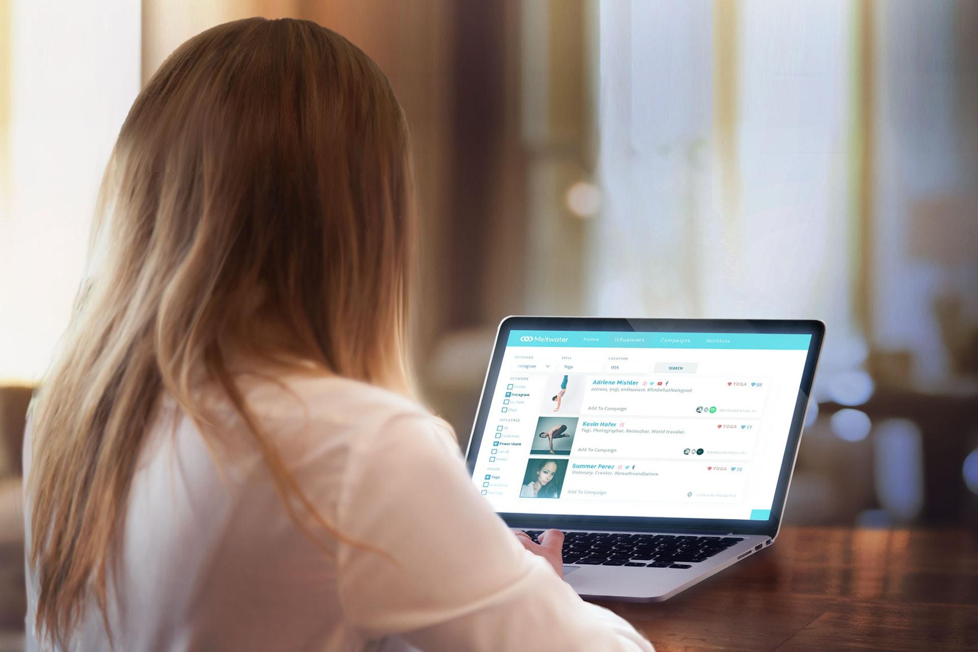 Henkilö tietokoneen edessä selkä kameraan päin, käyttää tietokoneella Meltwaterin Social Influencers vaikuttajamarkkinoinnin palvelua.