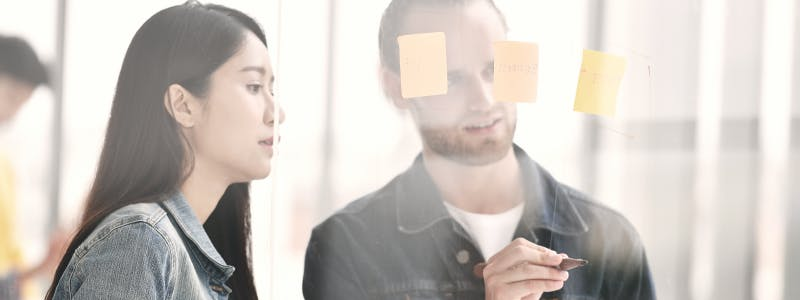 two people with sticky notes on glass wall for planning a facebook marketing strategy