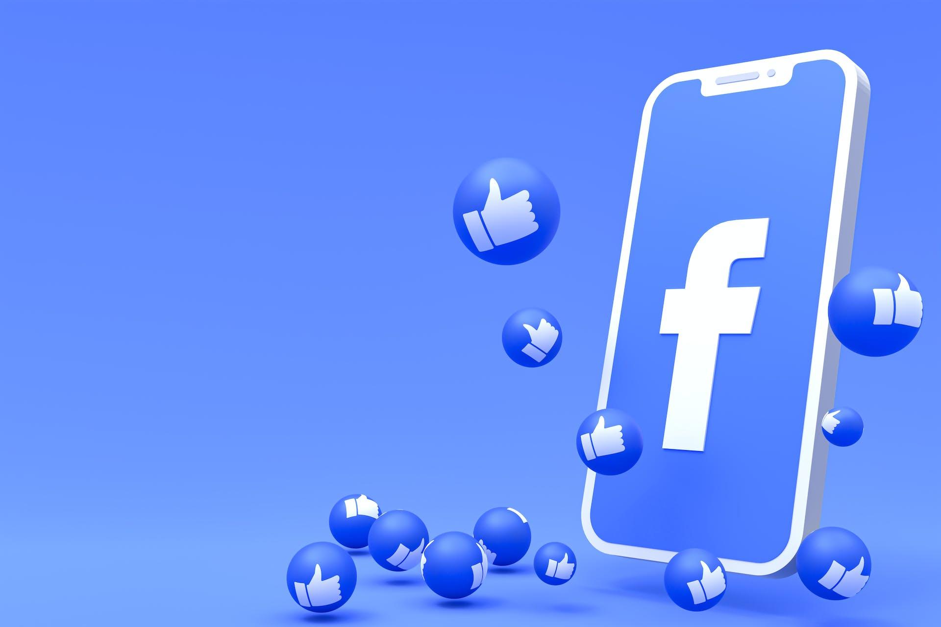 """Blauer Hintergrund, davor ein Smartphone mit Facebook-Logo auf dem Bildschirm und rundherum sind blaue Blasen auf denen man einen """"Daumen-hoch"""" sieht"""