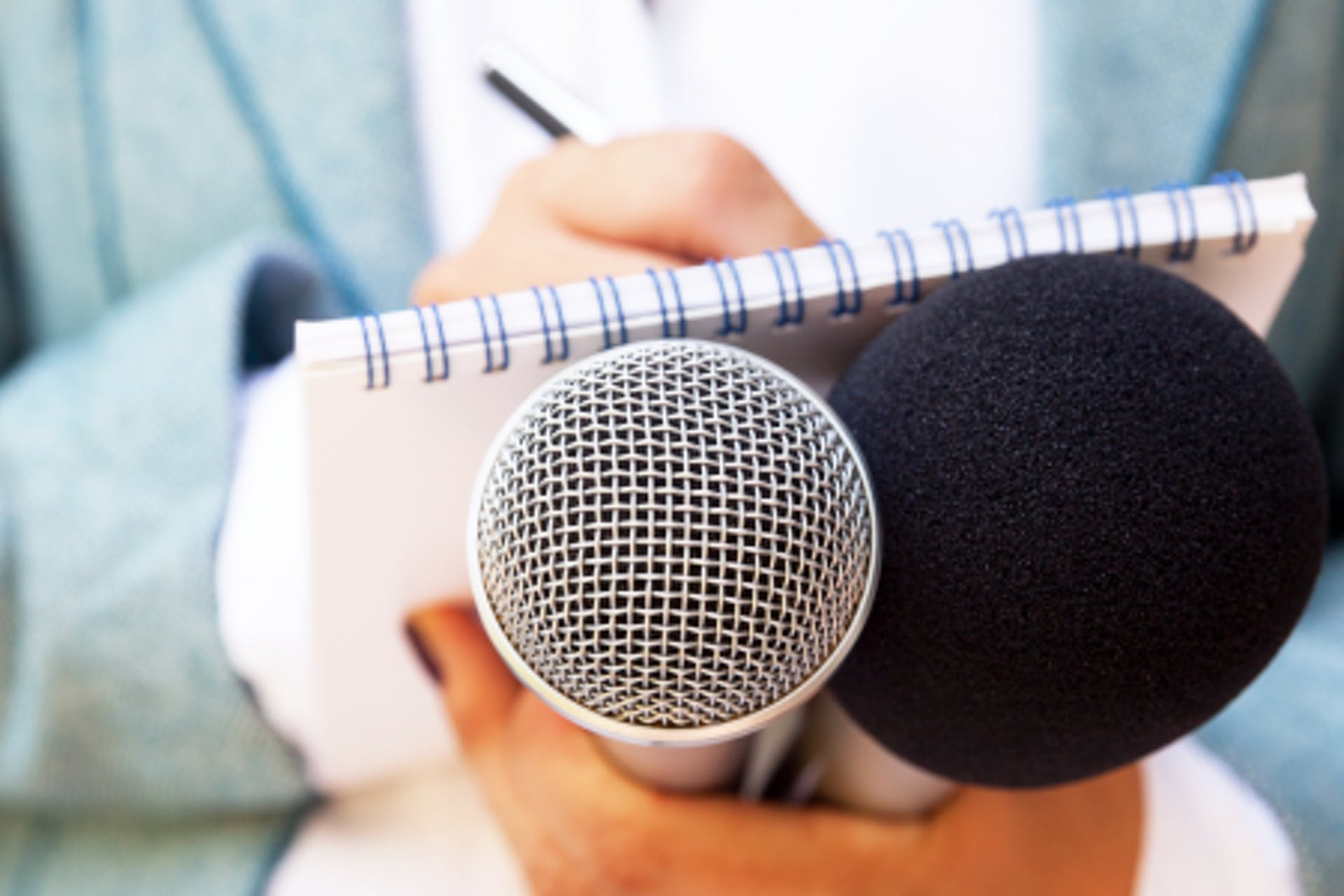 A reporter writing in a notepad while holding two microphones